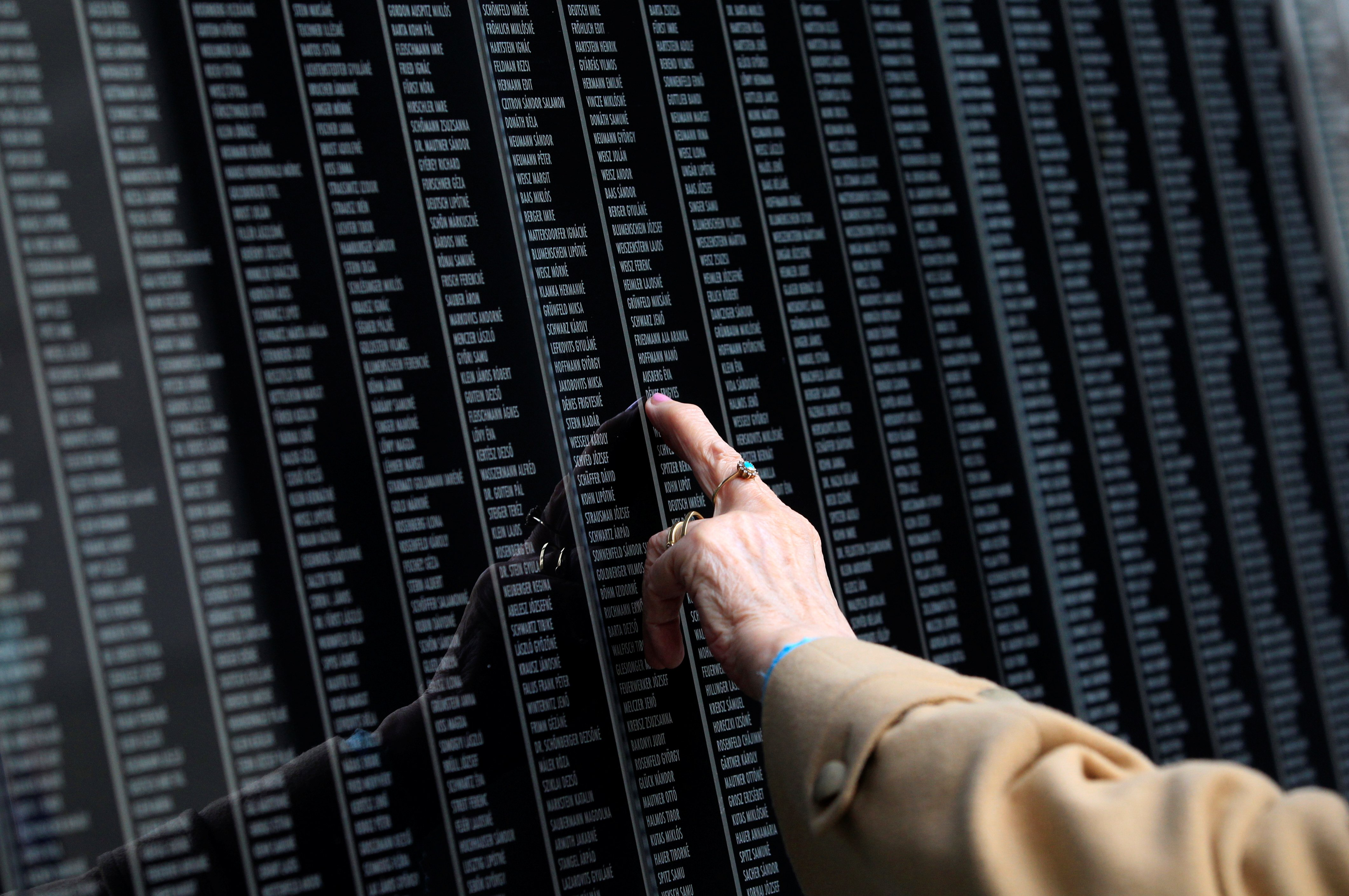 A woman touches a wall bearing the names of victims, during the Holocaust memorial day at Holocaust Memorial Centre in Budapest, Hungary April 16, 2018. REUTERS/Bernadett Szabo
