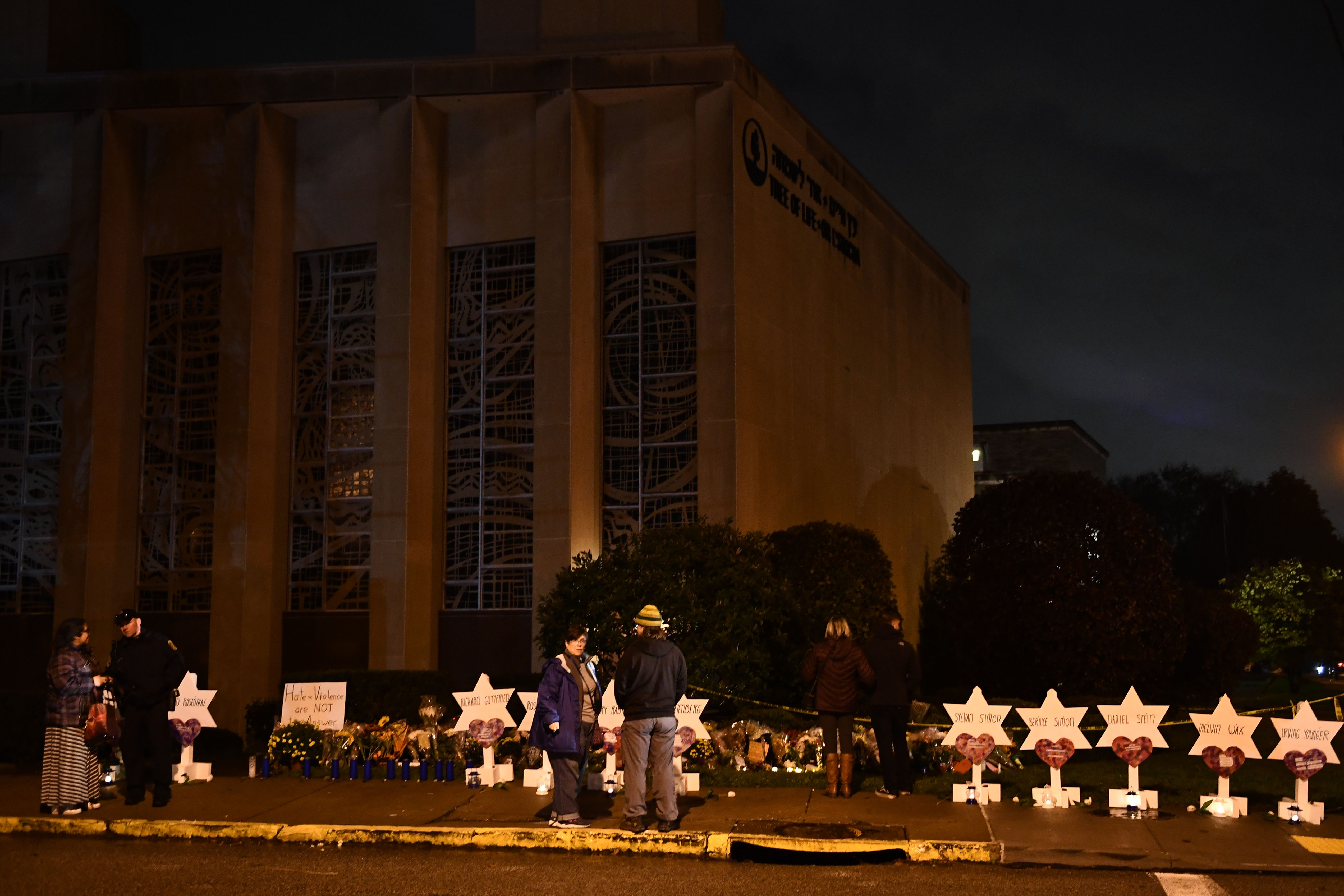 "People stand in front of a memorial on October 28, 2018, at the Tree of Life synagogue after a shooting there left 11 people dead in the Squirrel Hill neighborhood of Pittsburgh on October 27. - A man suspected of bursting into a Pittsburgh synagogue during a baby-naming ceremony and gunning down 11 people has been charged with murder, in the deadliest anti-Semitic attack in recent US history. The suspect -- identified as a 46-year-old Robert Bowers -- reportedly yelled ""All Jews must die"" as he sprayed bullets into the Tree of Life synagogue during Sabbath services on Saturday before exchanging fire with police, in an attack that also wounded six people.(BRENDAN SMIALOWSKI/AFP/Getty Images)"