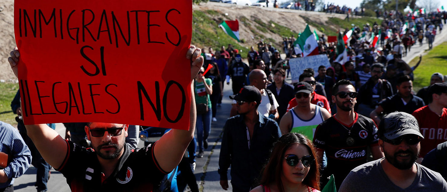 "A demonstrator holding a placard that reads, ""Immigrants yes, illegals not"" attends to a protest against migrants who are part of a caravan traveling en route to the United States, in Tijuana, Mexico November 18, 2018. REUTERS/Carlos Garcia Rawlins"