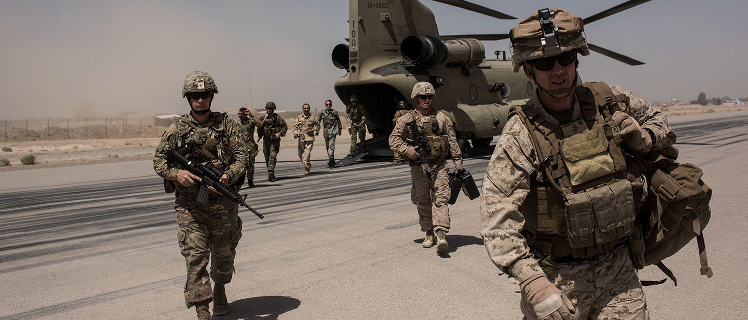 U.S. service members walk off a helicopter on the runway at Camp Bost on September 11, 2017 in Helmand Province, Afghanistan. About 300 marines are currently deployed in Helmand Province in a train, advise, and assist role supporting local Afghan security forces. (Photo by Andrew Renneisen/Getty Images)