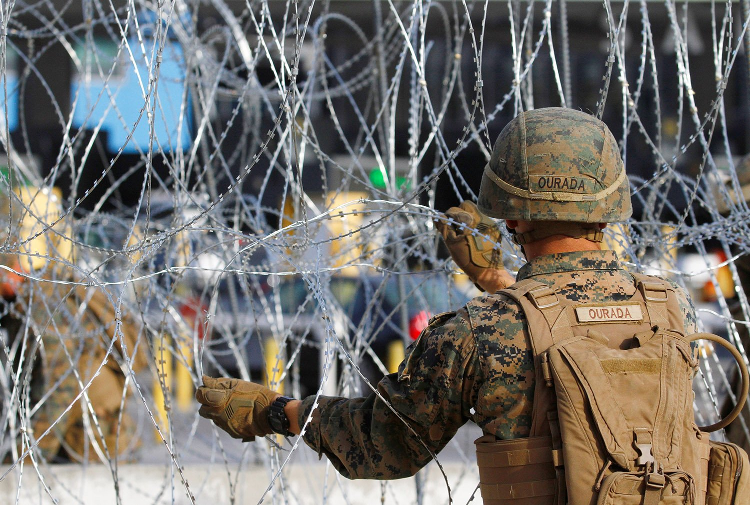 A U.S. Marine sets up a barricade with concertina wire, at the border between Mexico and the U.S., in preparation for the arrival of migrants, in Tijuana, Mexico November 13, 2018. REUTERS/Jorge Duenes