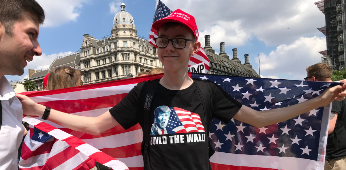 Pro Trump Protester demanding to build the wall, with a MAGA hat and a US flag. Shutterstock