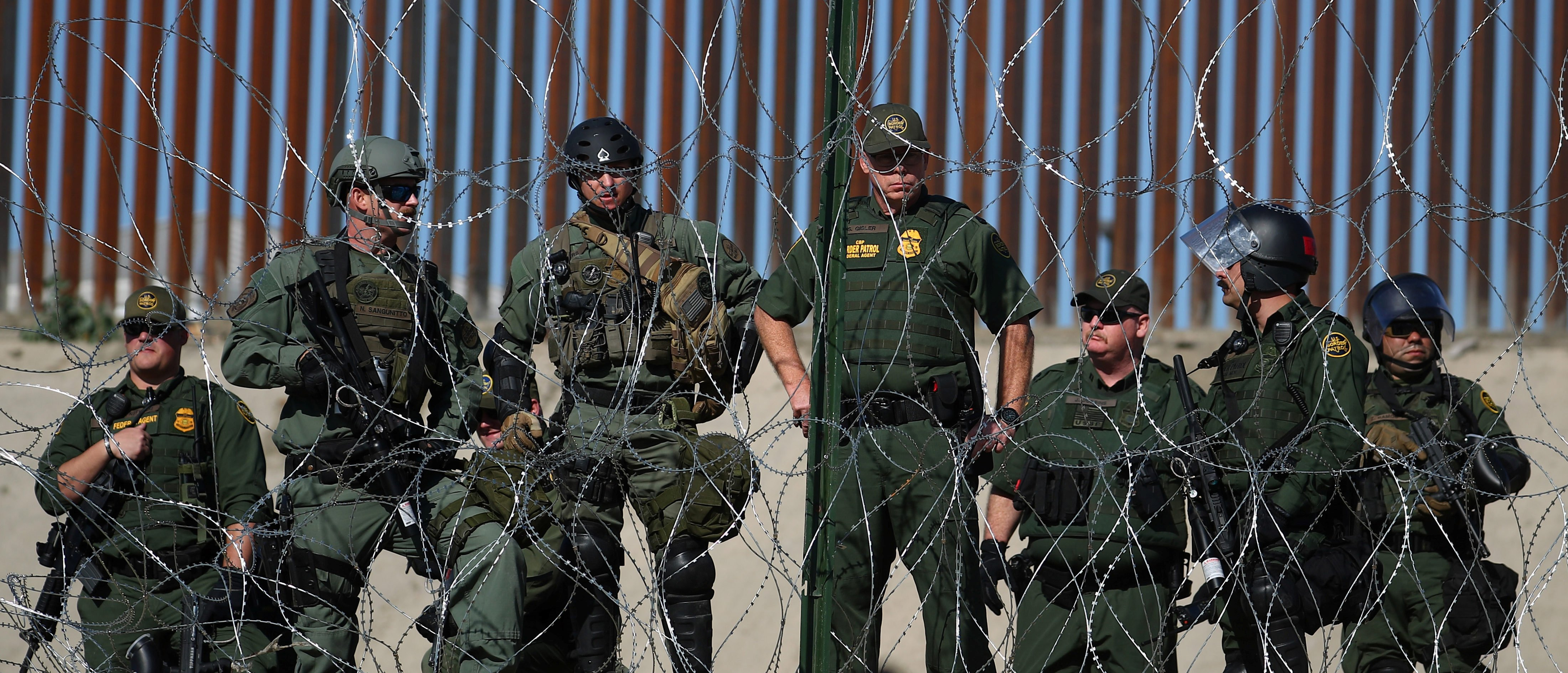 U.S border patrol stand near the border fence between Mexico and the United States as migrants stand near by in Tijuana, Mexico, November 25, 2018. REUTERS/Hannah McKay