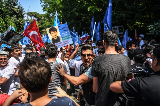 Turkish plain clothes police officers try push back demonstrators during a protest of supporters of the mostly Muslim Uighur minority and Turkish nationalists to denounce China's treatment of ethnic Uighur Muslims during a deadly riot in July 2009 in Urumqi, in front of the Chinese consulate in Istanbul, on July 5, 2018. - Nearly 200 people died during a series of violent riots that broke out on July 5, 2009 over several days in Urumqi, the capital city of the Xinjiang Uyghur Autonomous Region, in northwestern China, between Uyghurs and Han people. (OZAN KOSE/AFP/Getty Images)