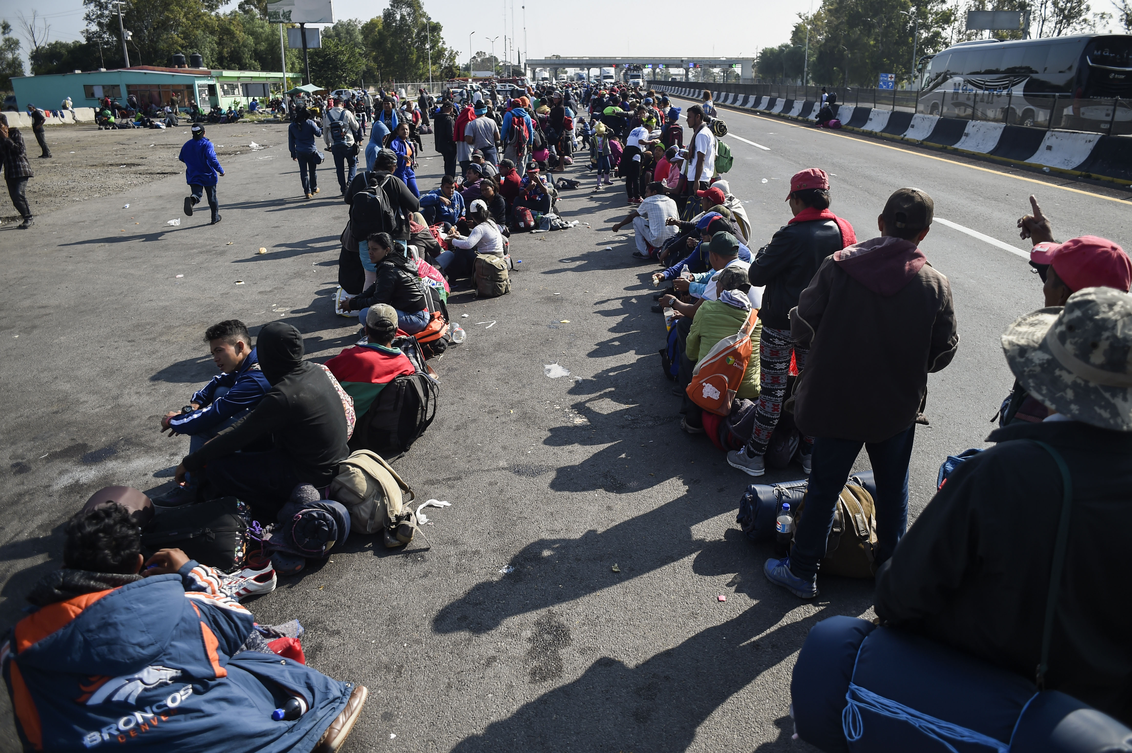 Central American migrants taking part in a caravan to the US, queue along the highway to get a ride to Irapuato in the state of Guanajuato on November 11, 2018 after spending the night in Queretaro in central Mexico. (ALFREDO ESTRELLA/AFP/Getty Images)