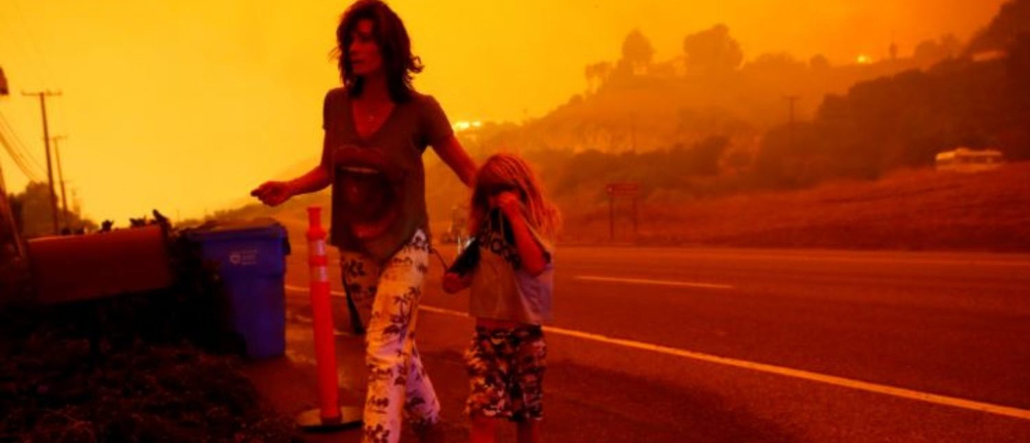 Gabi and Jonah Frank walk on Pacific Coast Highway as the Woolsey Fire threatens their home in Malibu, California, U.S. November 9, 2018. The fire destroyed dozens of structures, forced thousands of evacuations and closed a major freeway. REUTERS/Eric Thayer