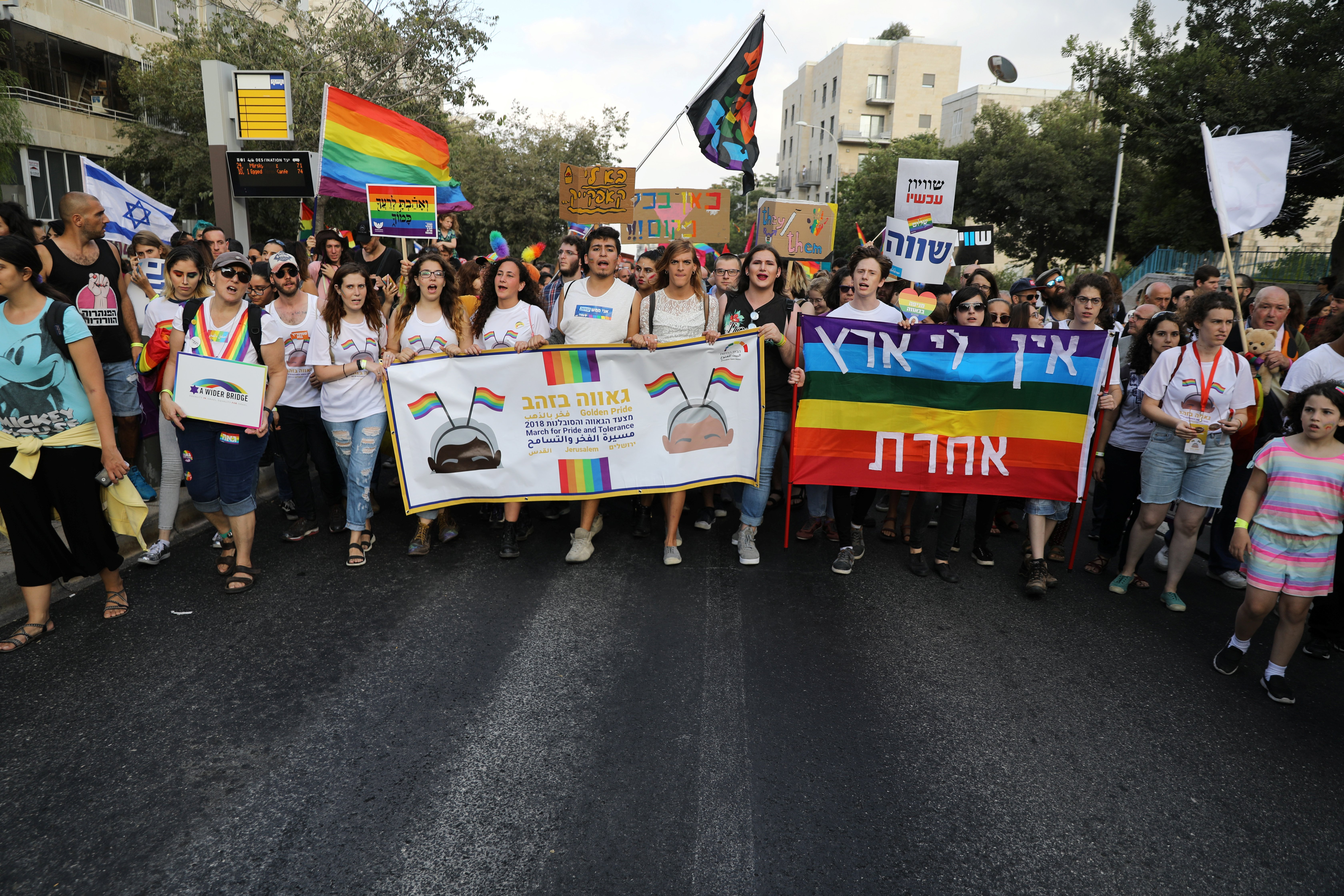 "Participants hold banners as they take part in Jerusalem's 17th annual Gay Pride Parade August 2, 2018. The banner on the right reads in Hebrew, "" I don't have another country"". REUTERS/Ammar Awad"