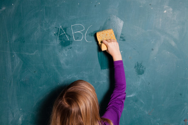 Young girl wiping letters written in chalk (Shutterstock/Elina Manninen)