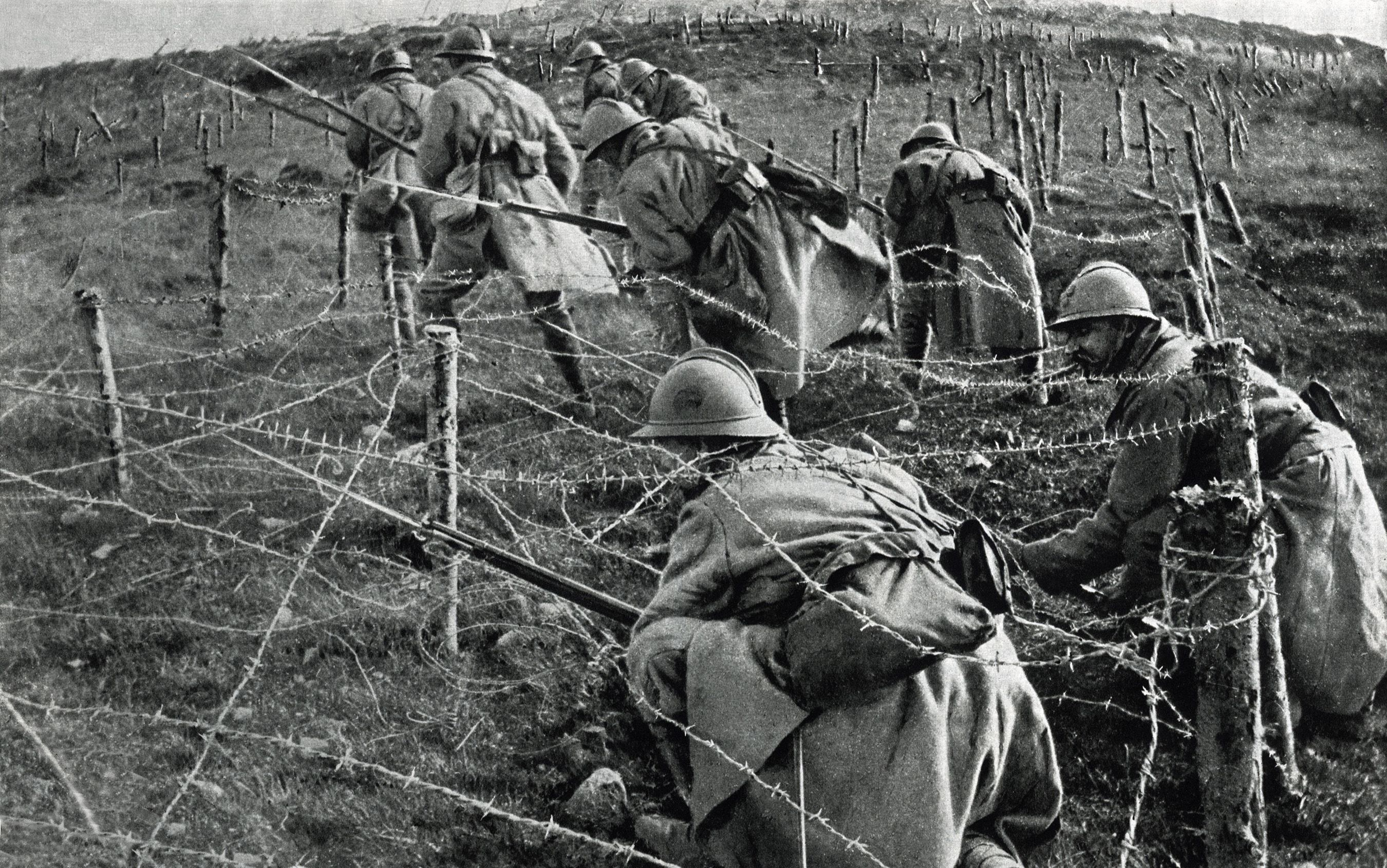 French soldiers crawling through their own barbed wire entanglements as they begin an attack on enemy trenches. April-June, 1916 (Everett Historical/Shutterstock)