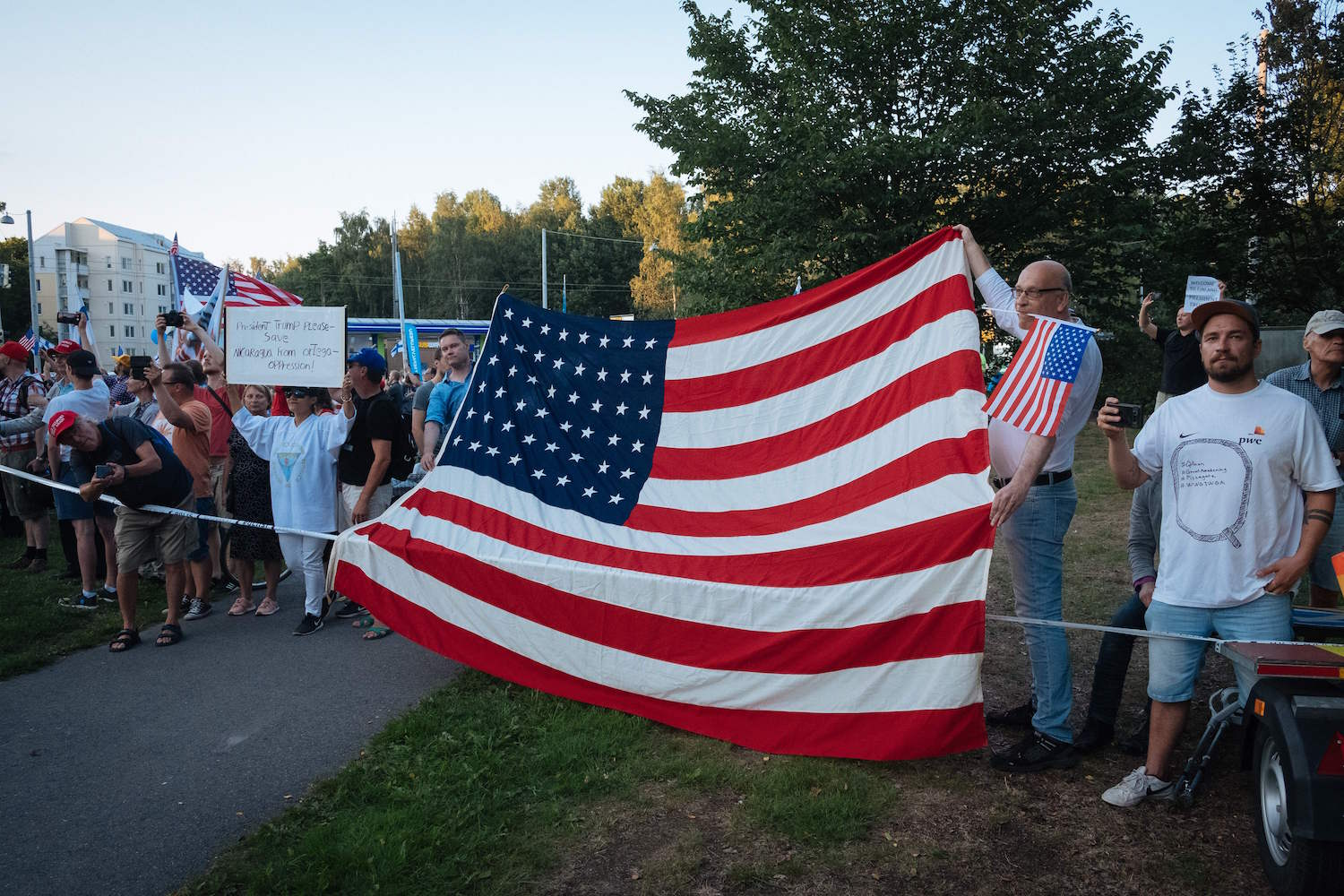 Supporters of US President Donald Trump hold an US flag as the Presidential cars passes by in Helsinki, Finland on July 15, 2018, on the eve of the meeting between the US President and his Russian counterpart. (ALESSANDRO RAMPAZZO/AFP/Getty Images)