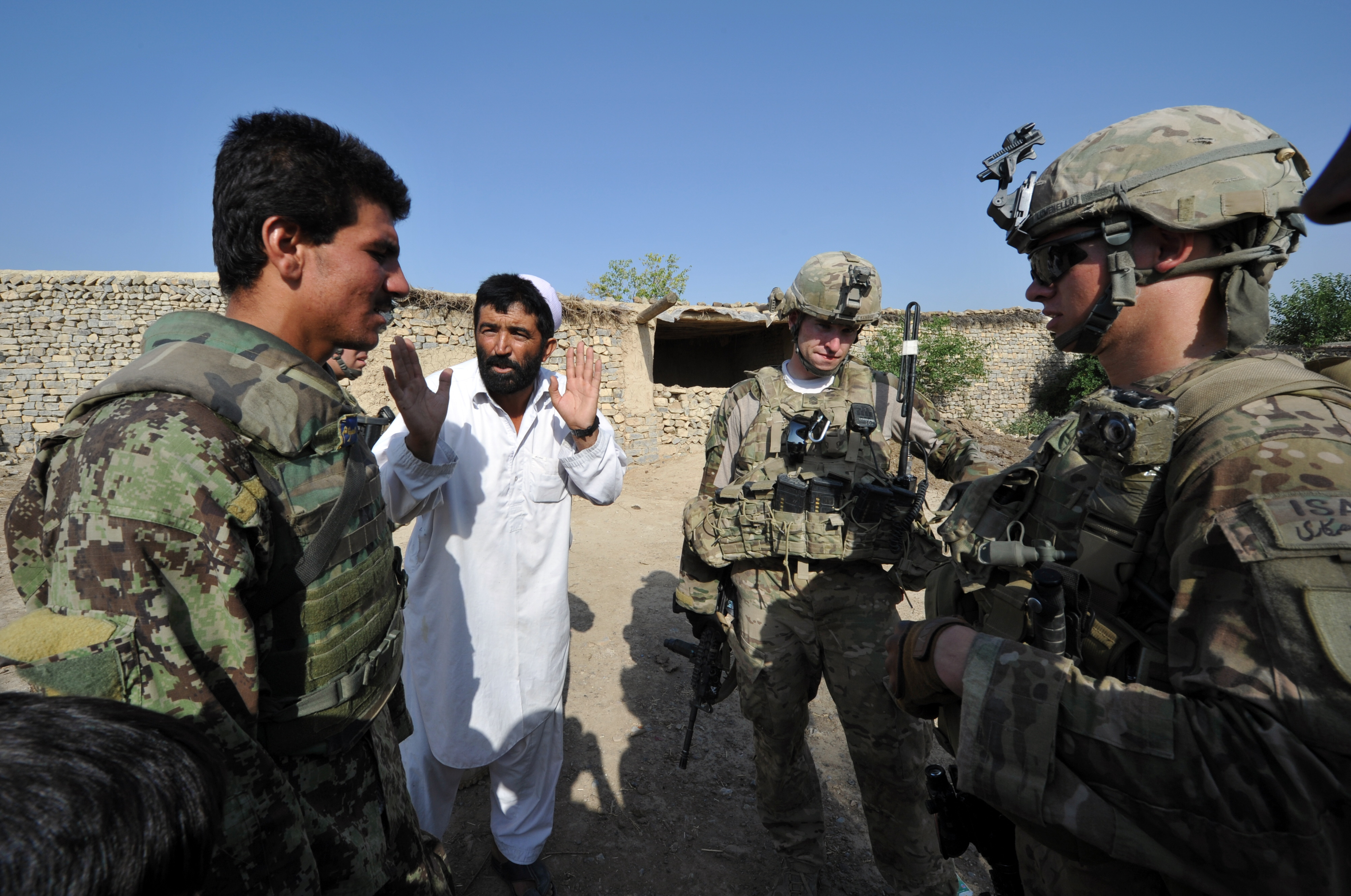 An Afghan soldier (L) serves an interpreter as a civilian talks to U.S. soldiers from Viper Company (Bravo), 1-26 Infantry during a patrol at a village near Combat Outpost (COP) Sabari in Khost province in eastern Afghanistan June 19, 2011. (TED ALJIBE/AFP/Getty Images)