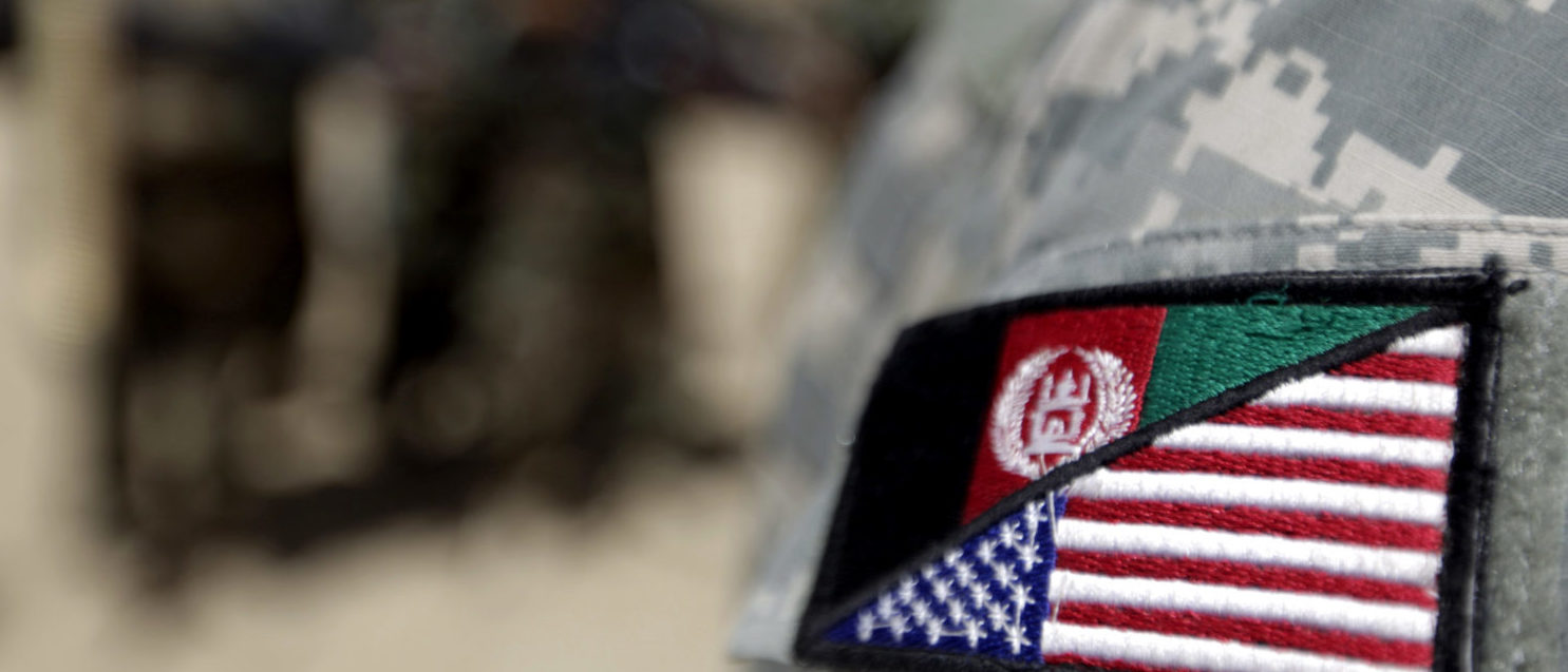 An Afghan interpreter working with the 101st Airborne Division Alpha Battery 1-320th displays a patch showing the Afghan and US flags at Combat Outpost Nolen on the outskirts of Arghandab valley's Jellawar town on September 9, 2010. The United States and NATO have 150,000 troops in Afghanistan aiming to quell the insurgency that began soon after the Taliban regime was overthrown in a US-led invasion in late 2001. (PATRICK BAZ/AFP/Getty Images)