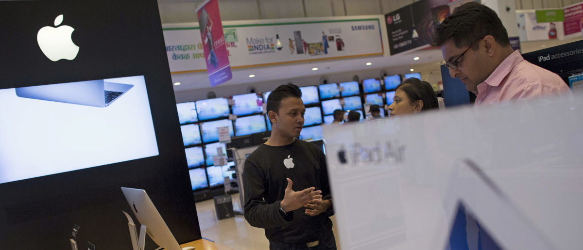 An Apple salesperson speaks to customers at an electronics store in Mumbai, India, July 23, 2015. REUTERS/Danish Siddiqui