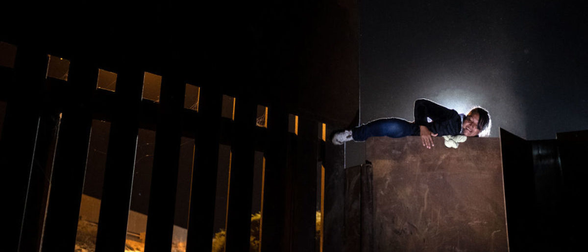 TOPSHOT - A woman who has been traveling in a caravan of Central American migrants hoping to get to the United States, climbs the metal barrier separating Mexico and the US to cross from Playas de Tijuana in Mexico into the US, on December 3, 2018. (GUILLERMO ARIAS/AFP/Getty Images)