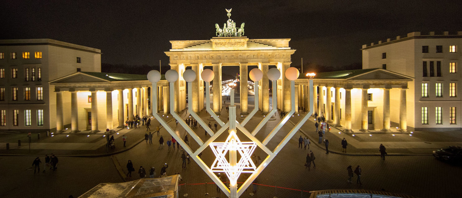 BERLIN, GERMANY - DECEMBER 16: The first lamp of a large scale menorah in front of the Brandenburg Gate lights after it was lights by Rabbis Yehuda Teichtal and German Interior Minist Lothar de Maiziere on December 16, 2014 in Berlin, Germany. It is the first day in the celebration of Hanukkah. Berlin is home to a growing Jewish population, many of whom are immigrants from the former Soviet Union, after the local Jewish community was devastated by the Holocaust before and during World War II. (Photo by Carsten Koall/Getty Images)