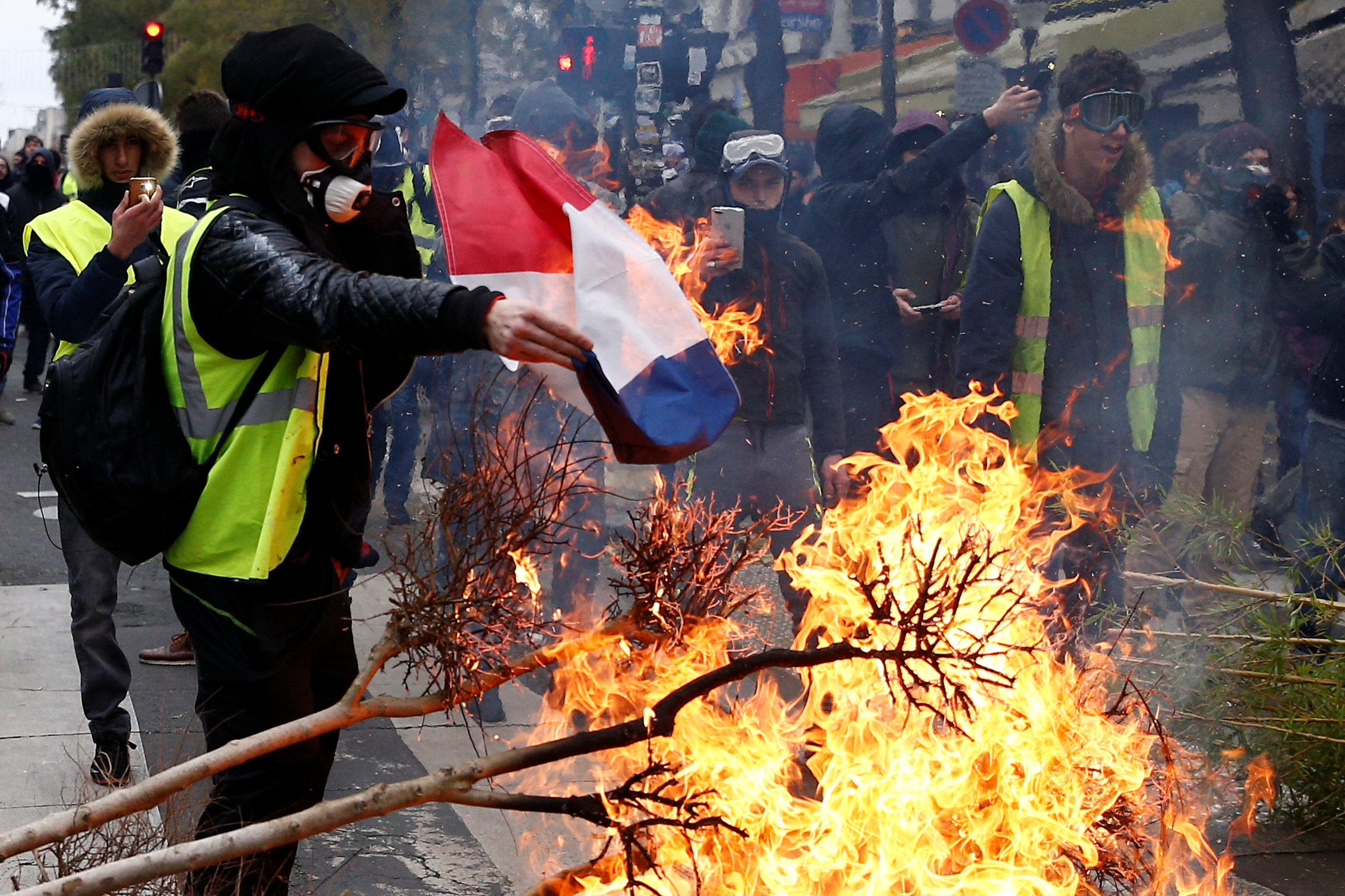 "A protester wearing a yellow vest burns a French flag at a barricade during clashes with police as part of a national day of protest by the ""yellow vests"" movement in Paris, France, December 8, 2018. REUTERS/Stephane Mahe"