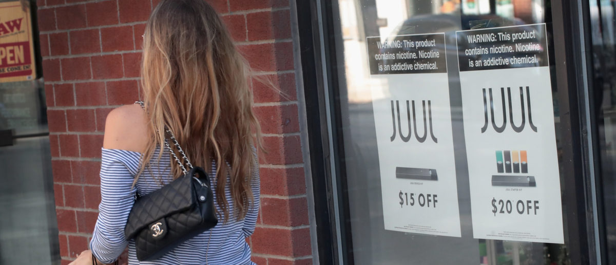 Signs in the window of the Smoke Depot advertise electronic cigarettes and pods by Juul, the nation's largest maker of e-cigarette products, on September 13, 2018 in Chicago, Illinois. (Photo by Scott Olson/Getty Images)