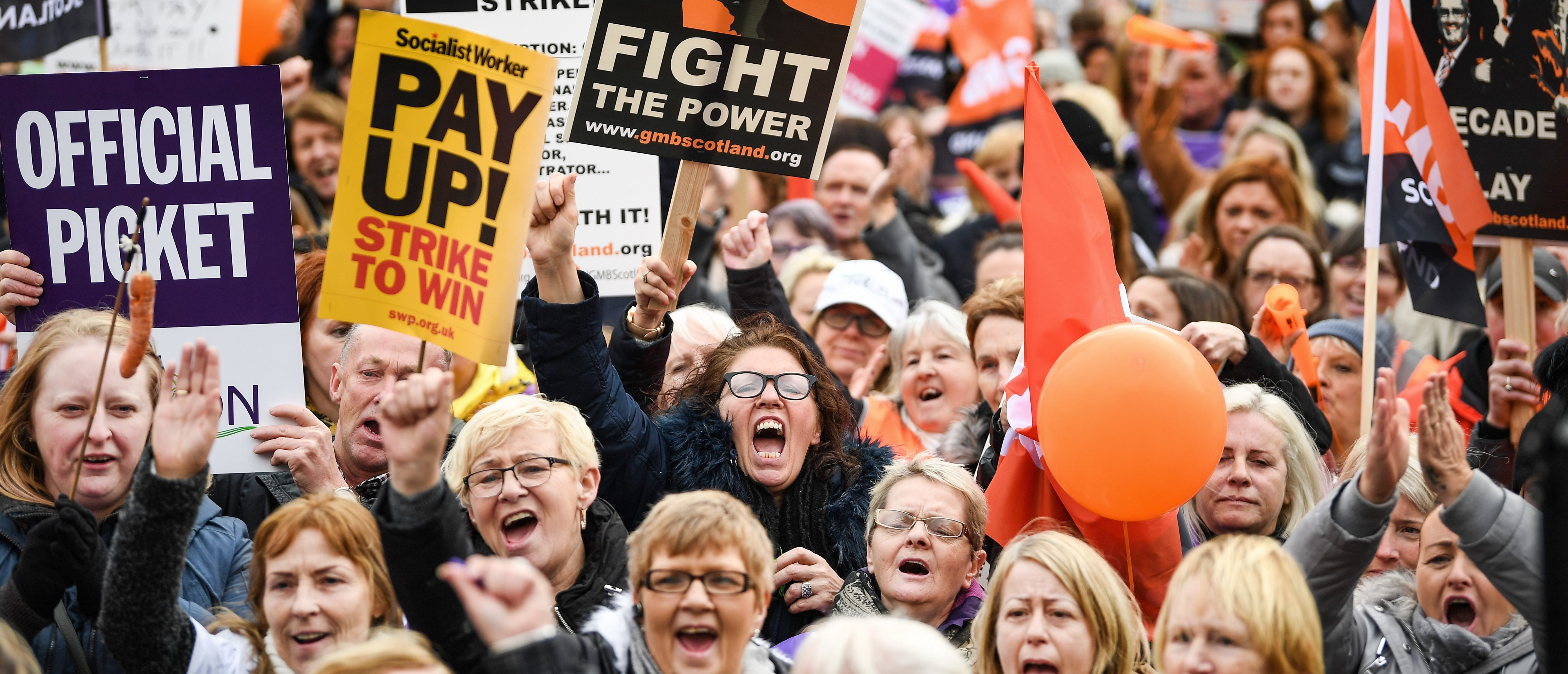 GLASGOW, SCOTLAND - OCTOBER 23: Demonstrators hold placards as they attend a rally in George Square following a march for equal pay for Glasgow council workers on October 23, 2018 in Glasgow, Scotland. Schools and home-care services were disrupted as an estimated 8,000 workers joined a 48-hour walkout, aimed at spurring the settlement of equal-pay claims from thousands of female workers. (Photo by Jeff J Mitchell/Getty Images)