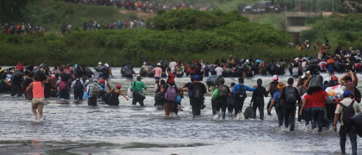 Salvadorean migrants heading in a caravan to the US, cross the Suchiate River to Mexico, as seen from Ciudad Tecun Uman, Guatemala, on November 02, 2018. - According to the Salvadorean General Migration Directorate (DGME), over 1,700 Salvadoreans left the country in two caravans and entered Guatemala Wednesday, in an attempt to reach the US. (Photo by MARVIN RECINOS / AFP)