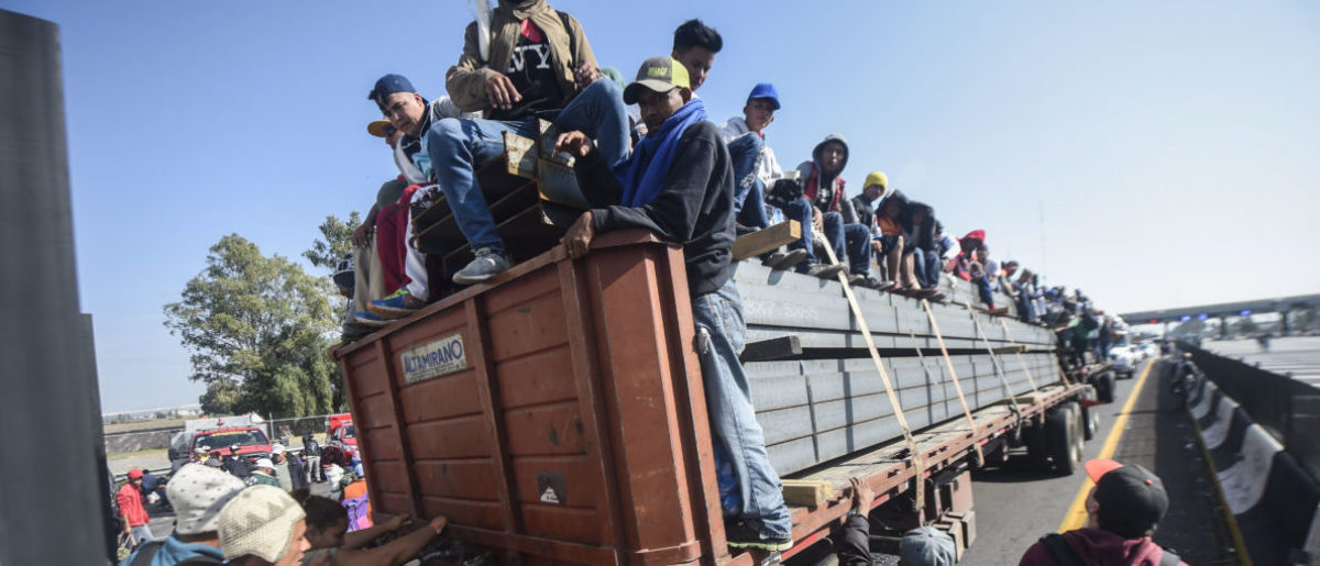 Central American migrants -- mostly Honduran -- taking part in a caravan to the US, are pictured on board a truck heading to Irapuato in the state of Guanajuato on Nov. 11, 2018 after spending the night in Queretaro in central Mexico. (Photo by ALFREDO ESTRELLA / AFP)