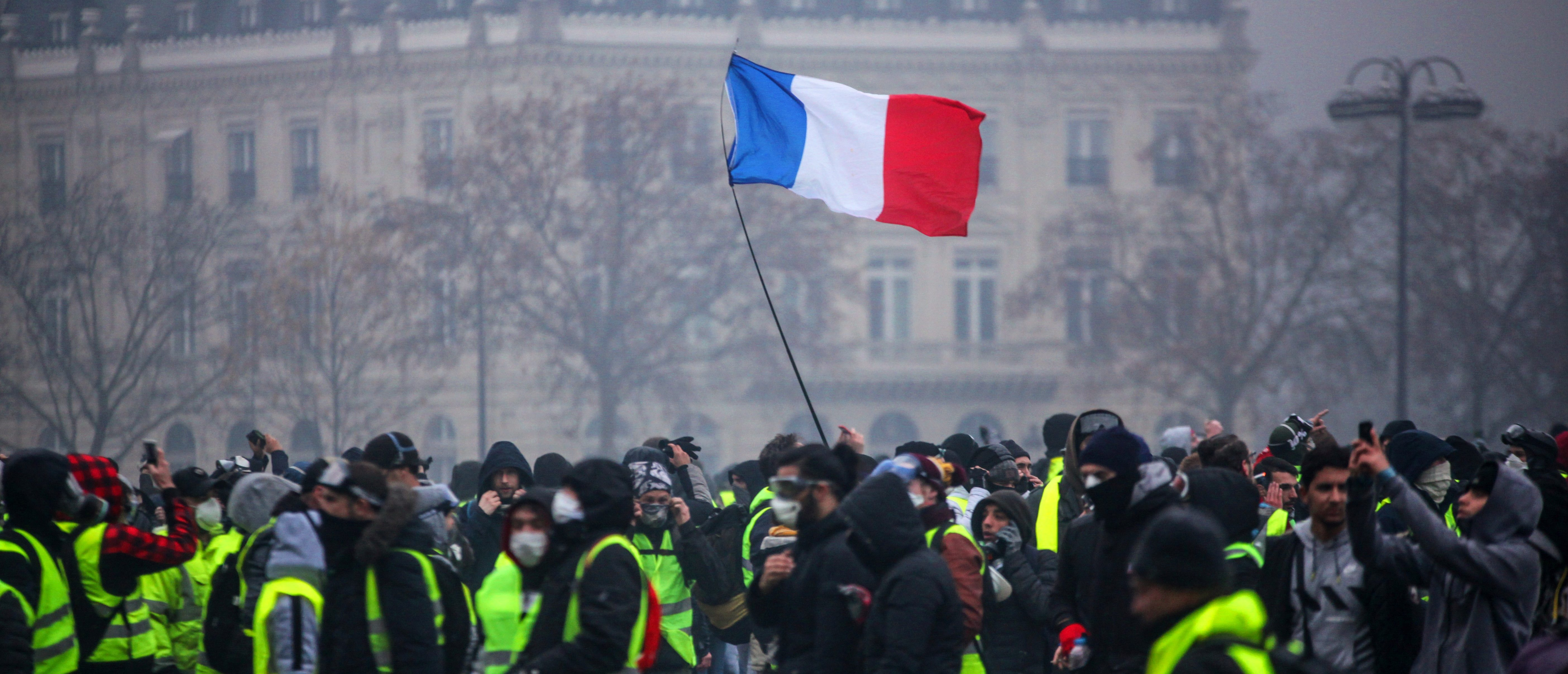 "TOPSHOT - Demonstrators gather near the Arc de Triomphe as a French flag floats during a protest of Yellow vests (Gilets jaunes) against rising oil prices and living costs, on December 1, 2018 in Paris. - Anti-government protesters torched dozens of cars and set fire to storefronts during daylong clashes with riot police across central Paris on December 1, as thousands took part in fresh ""yellow vest"" protests against high fuel taxes. (Photo by - / AFP) (Photo credit should read -/AFP/Getty Images)"