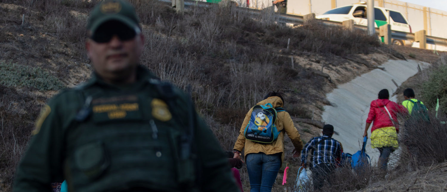 Central American migrants surrender to US Border Patrol agents after jumping over the metal barrier separating Playas de Tijuana in Mexico from the United States, on December 2, 2018, as seen from Playas de Tijuana. - Thousands of Central American migrants, mostly Hondurans, have trekked for over a month in the hopes of reaching the United States. (Photo by GUILLERMO ARIAS/AFP/Getty Images)