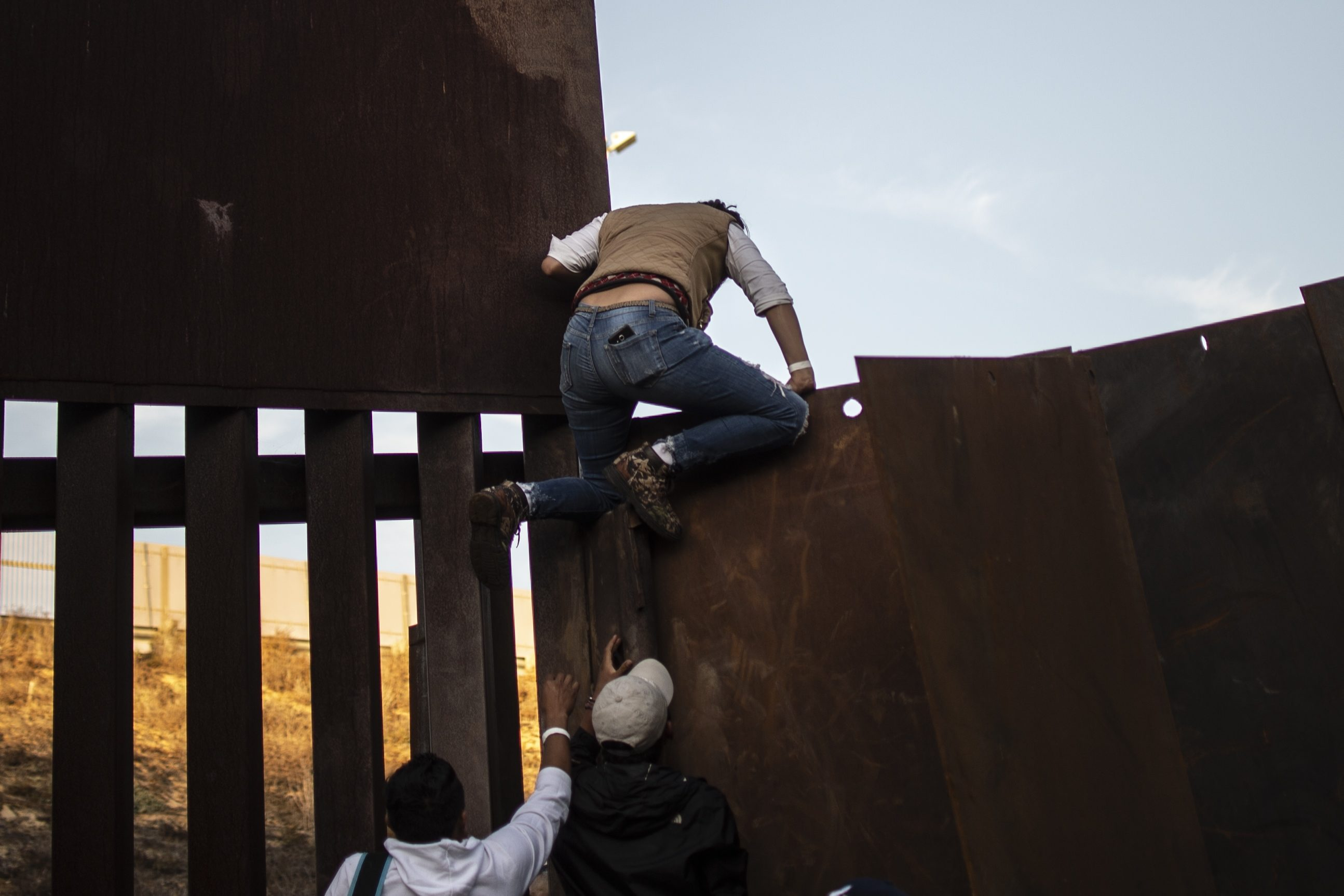 Central American migrants who have been travelling in a caravan hoping to get to the United States, climb the metal barrier separating Mexico and the US, in Playas de Tijuana, Mexico on December 2, 2018. (Photo credit should read PEDRO PARDO/AFP/Getty Images)