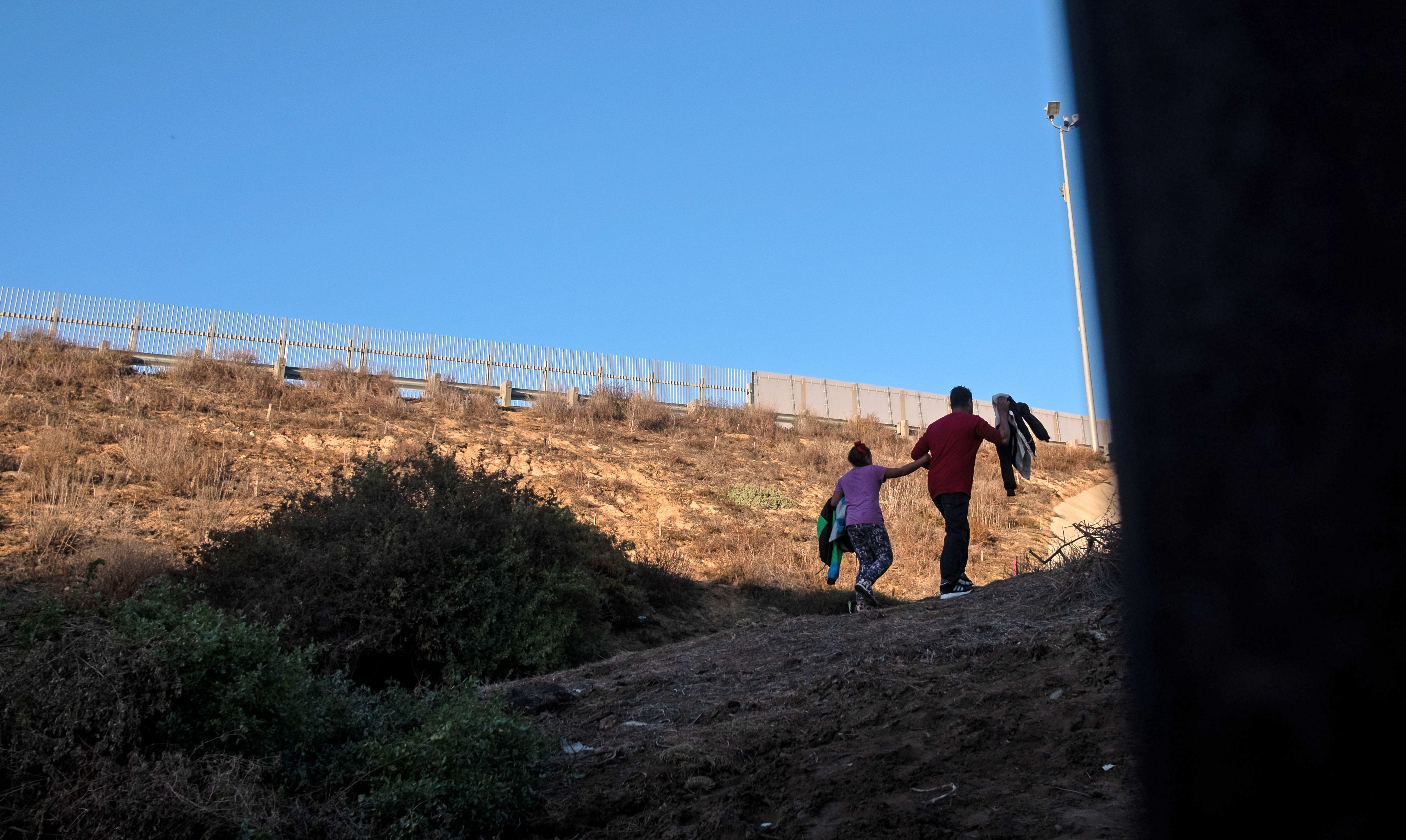 "Honduran Andrea Nicolle, 10, and her father Tony, traveling in a caravan of Central American migrants hoping to get to the United States, walk to surrender to the Border Patrol after crossing through a hole on the ground under the metal barrier separating Mexico and the US to cross from Playas de Tijuana in Mexico into the US, on December 4, 2018. - Mexico's new Foreign Minister Marcelo Ebrard met with US Secretary of State Mike Pompeo for a ""friendly"" meeting amid tensions over the migrant crisis at the border. Both countries are grappling with how to handle the thousands of Central American migrants who are camped at the common border -- in the short and long terms. (Photo by GUILLERMO ARIAS/AFP/Getty Images)"