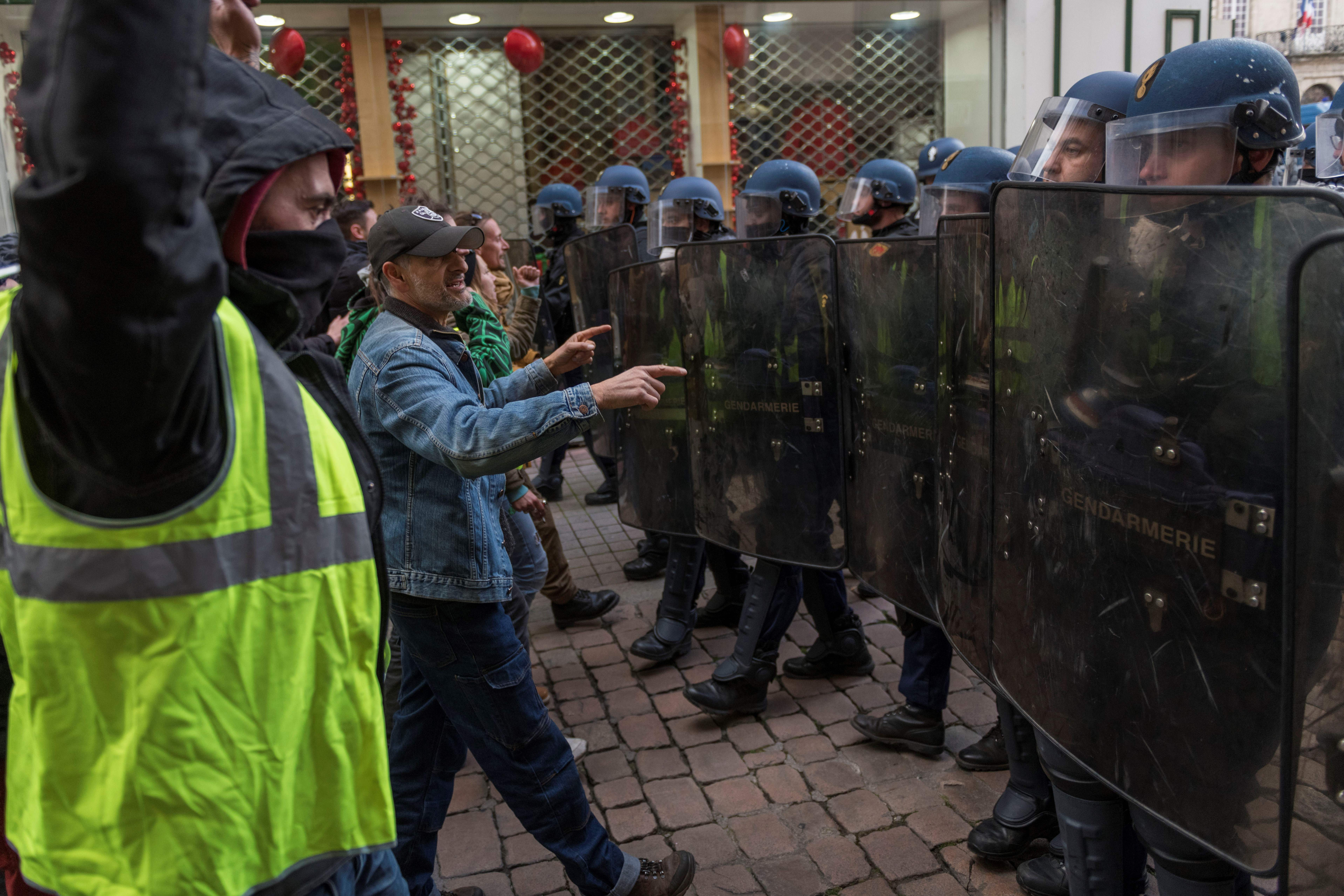 "Protestors wearing yellow vests (gilets jaunes), face French riot police officers during a demonstration against rising costs of living they blame on high taxes, in Le Puy-en-Velay, on December 8, 2018, - The ""yellow vest"" movement in France originally started as a protest about planned fuel hikes but has morphed into a mass protest against President's policies and top-down style of governing. (Photo by Thierry Zoccolan / AFP)"