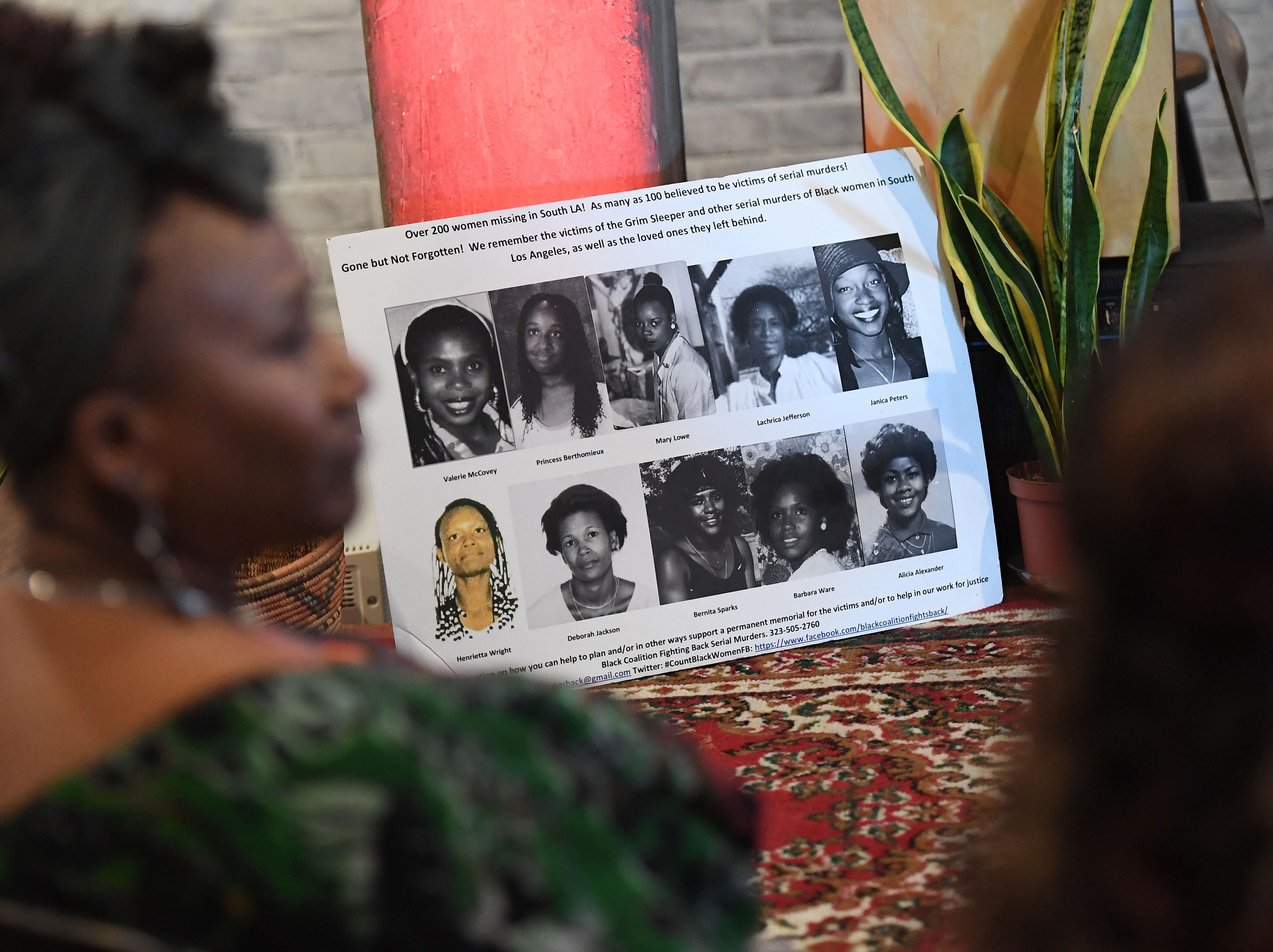 "People look at photos of known victims of serial killers Lonnie Franklin known as the ""Grim Sleeper"", Samuel Little and other Los Angeles serial killers at a memorial service in Los Angeles, California on December 8, 2018. (MARK RALSTON/AFP/Getty Images)"