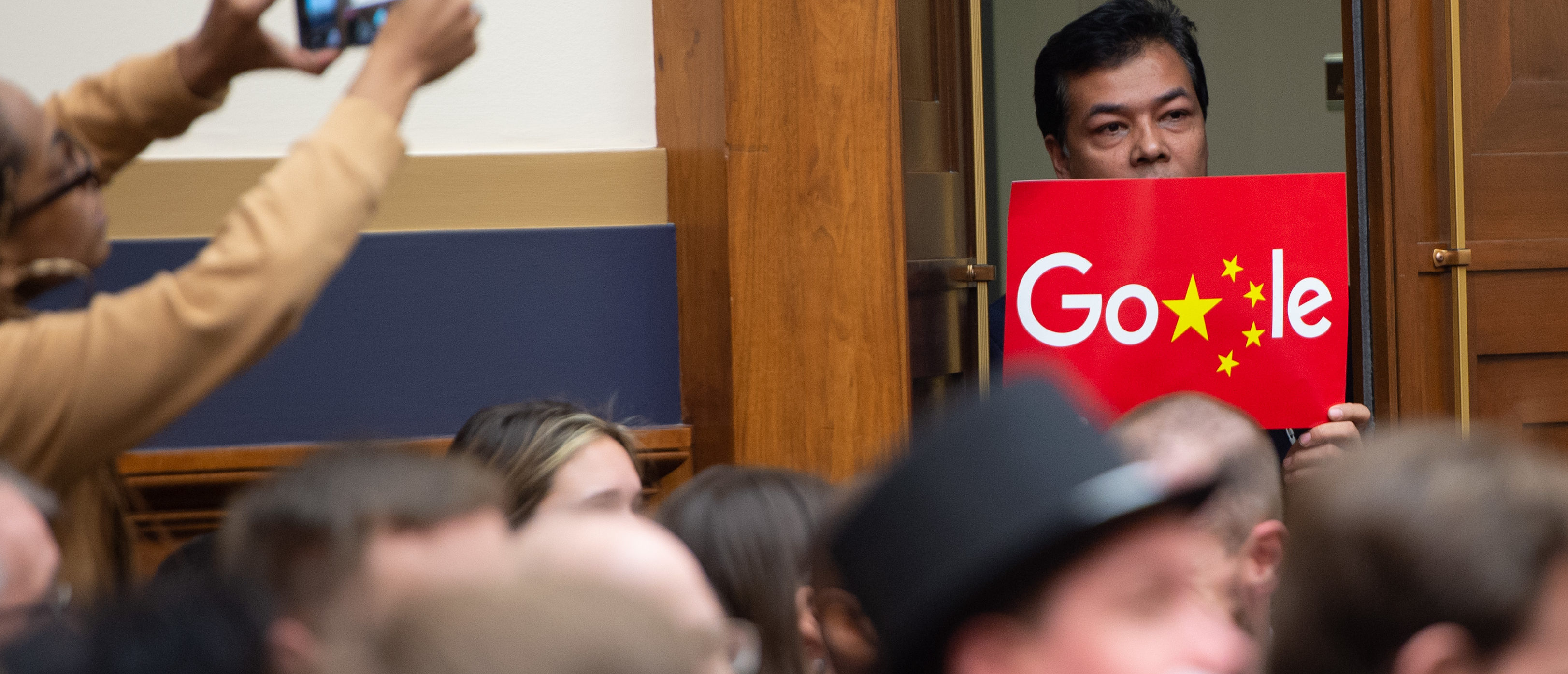"""A demonstrator holds a sign in protest as Google CEO Sundar Pichai testifies during a House Judiciary Committee hearing on Capitol Hill in Washington, DC, December 11, 2018. - Google chief executive Sundar Pichai was grilled by US lawmakers over allegations of """"political bias"""" by the internet giant, concerns over data security and its domination of internet search. (Photo by SAUL LOEB / AFP) (Photo credit should read SAUL LOEB/AFP/Getty Images)"""