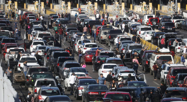 TIJUANA, MEXICO - NOVEMBER 25: People attempting to cross into the U.S. look on by their vehicles as the San Ysidro port of entry stands closed at the U.S.-Mexico border on November 25, 2018 in Tijuana, Mexico. Migrants circumvented a police blockade as they attempted to approach the El Chaparral port of entry and U.S. Customs and Border Protection temporarily closed the two ports of entry on the border with Tijuana in response. Around 6,000 migrants from Central America have arrived in the city with the mayor of Tijuana declaring the situation a 'humanitarian crisis'. (Photo by Mario Tama/Getty Images)