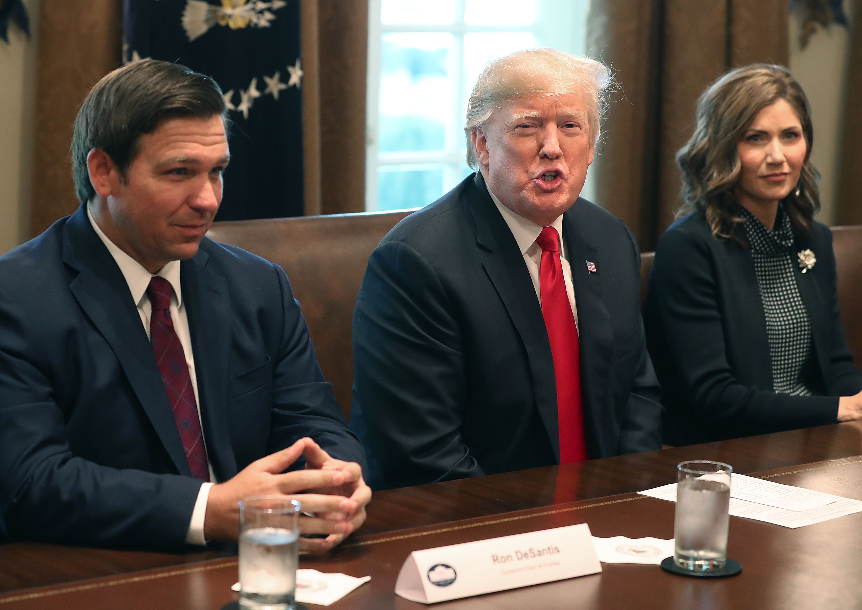 Florida Governor-elect Ron DeSantis (R) sits next to U.S. President Donald Trump and Governor of South Dakota-elect Kristi Noem during a meeting with Governors elects in the Cabinet Room at the White House on December 13, 2018 in Washington, DC. (Photo by Mark Wilson/Getty Images)