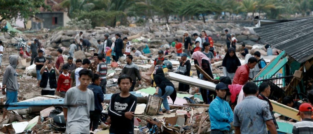TOPSHOT - Rescuers and residents look for survivors along the coast in South Lampung on South Sumatra on December 23, 2018, after the area was hit by a tsunami on December 22 following an eruption of the Anak Krakatoa volcano. - A volcano-triggered tsunami has left at least 222 people dead and hundreds more injured after slamming without warning into beaches around Indonesia's Sunda Strait, officials said on December 23, voicing fears that the toll would rise further. (Photo by Ferdi Awed / AFP)