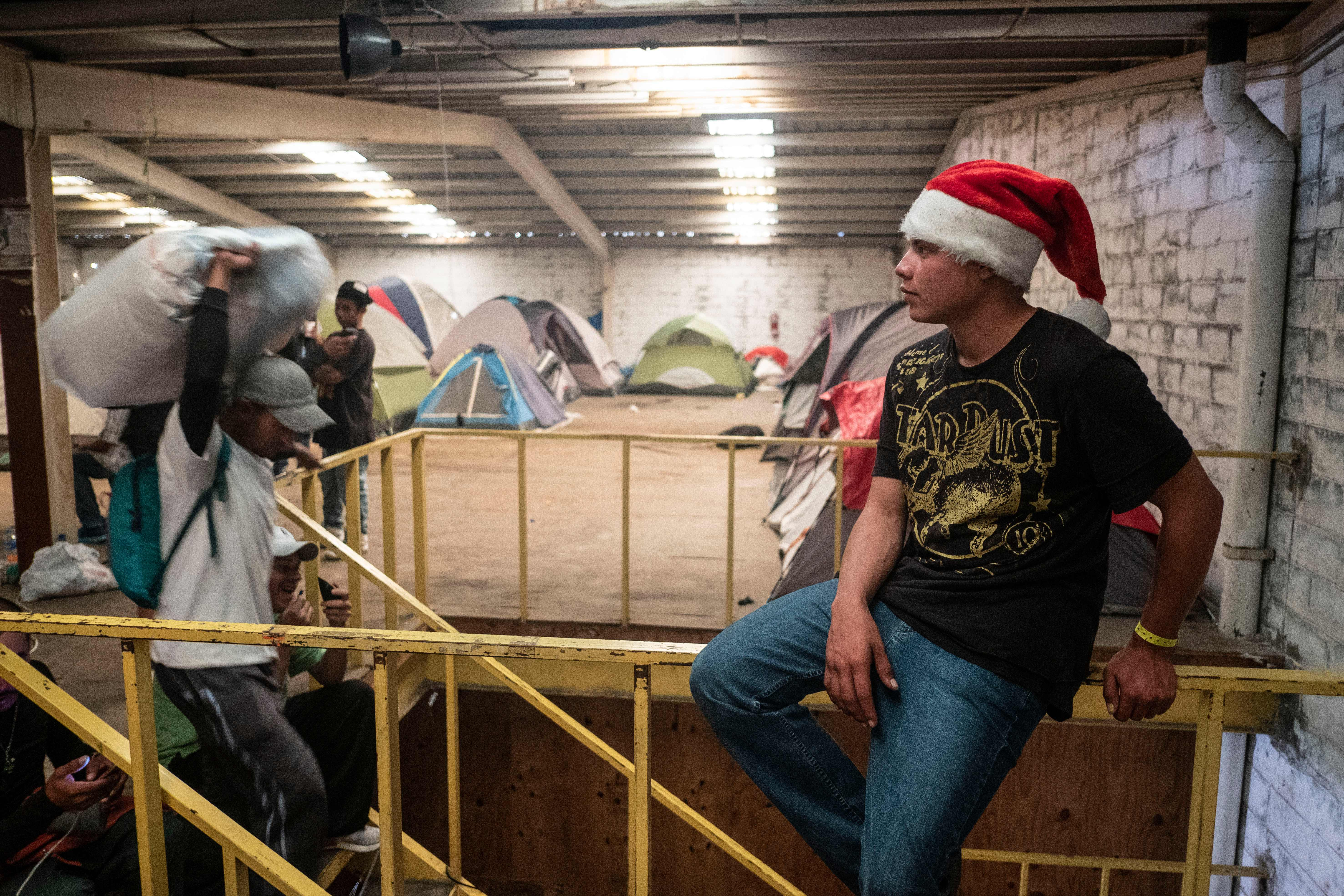Young men, part of the Central American migrants traveling to the United States, are seen on Christmas eve at a temporary shelter downtown Tijuana, Baja California state, Mexico on December 24, 2018. (Photo credit should read GUILLERMO ARIAS/AFP/Getty Images)