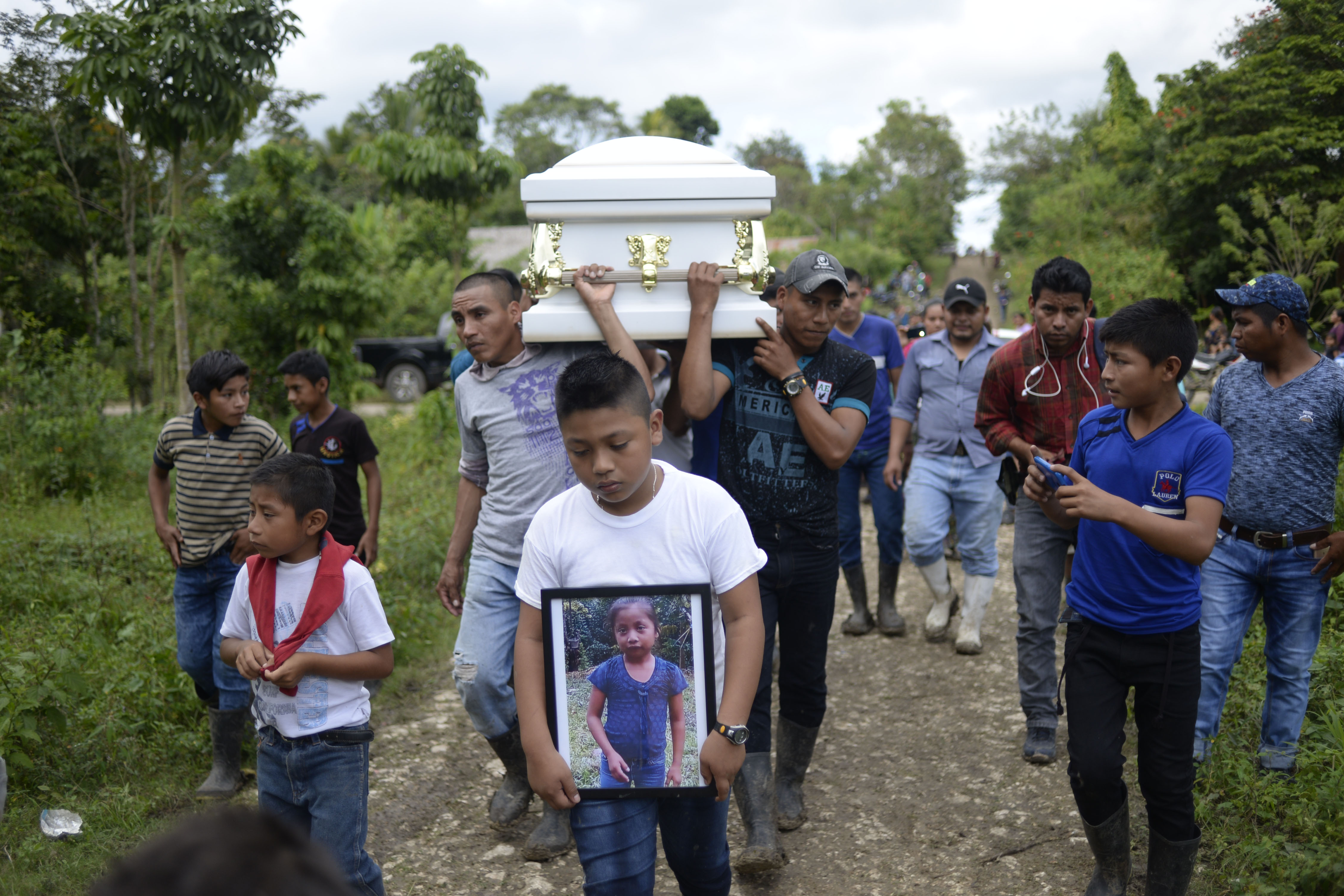 "TOPSHOT - A boy carries a picture of Guatemalan seven-year-old Jakelin Caal, who died in a Texas hospital two days after being taken into custody by US border patrol agents in a remote stretch of the New Mexico desert, as her coffin is taken from Raxruha to the cemetery in San Antonio Secortez, both villages in Alta Verapaz Department, 320 km north of Guatemala City, on December 25, 2018. - Jakelin Caal died after being arrested with her father and others crossing from Mexico into the US on December 6. Together they had travelled more than 3,000 km from their hometown of Raxruha, Guatemala. According to local media citing US Customs and Border Protection, the cause of death was ""dehydration and shock"". (Photo by JOHAN ORDONEZ/AFP/Getty Images)"