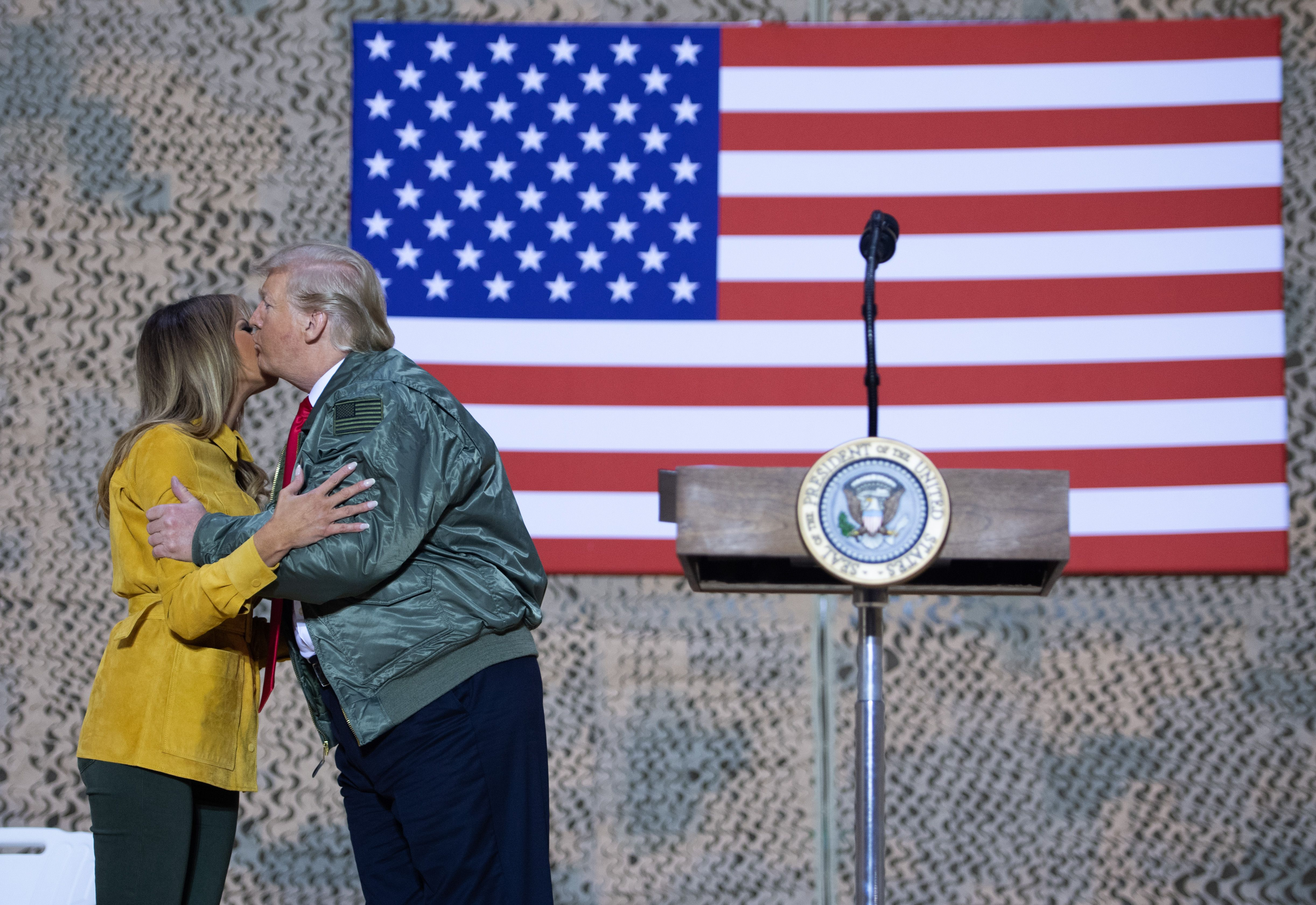 US President Donald Trump kisses First Lady Melania Trump as he speaks to members of the US military during an unannounced trip to Al Asad Air Base in Iraq, December 26, 2018. - President Donald Trump arrived in Iraq on his first visit to US troops deployed in a war zone since his election two years ago (Photo by SAUL LOEB / AFP)