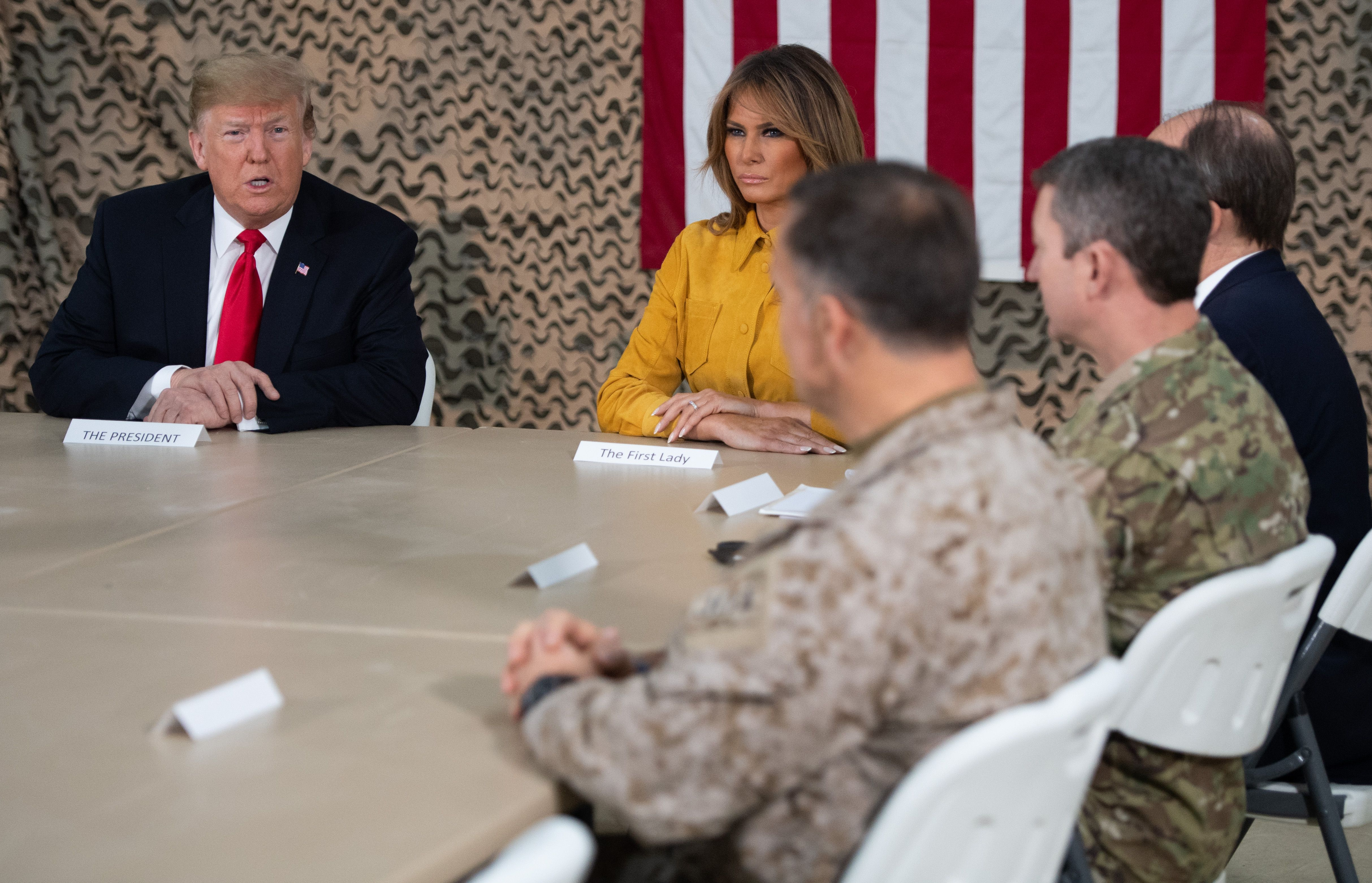 US President Donald Trump and First Lady Melania Trump attend a military briefing during an unannounced trip to Al Asad Air Base in Iraq on December 26, 2018. - President Donald Trump arrived in Iraq on his first visit to US troops deployed in a war zone since his election two years ago (Photo by SAUL LOEB/AFP/Getty Images)