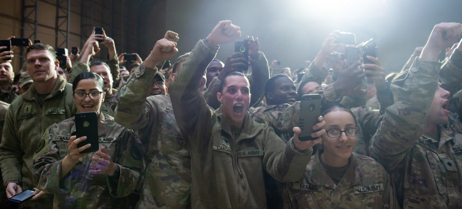 Members of the US military cheer as US President Donald Trump arrives to speak during an unannounced trip to Al Asad Air Base in Iraq on December 26, 2018. (Photo by SAUL LOEB / AFP)