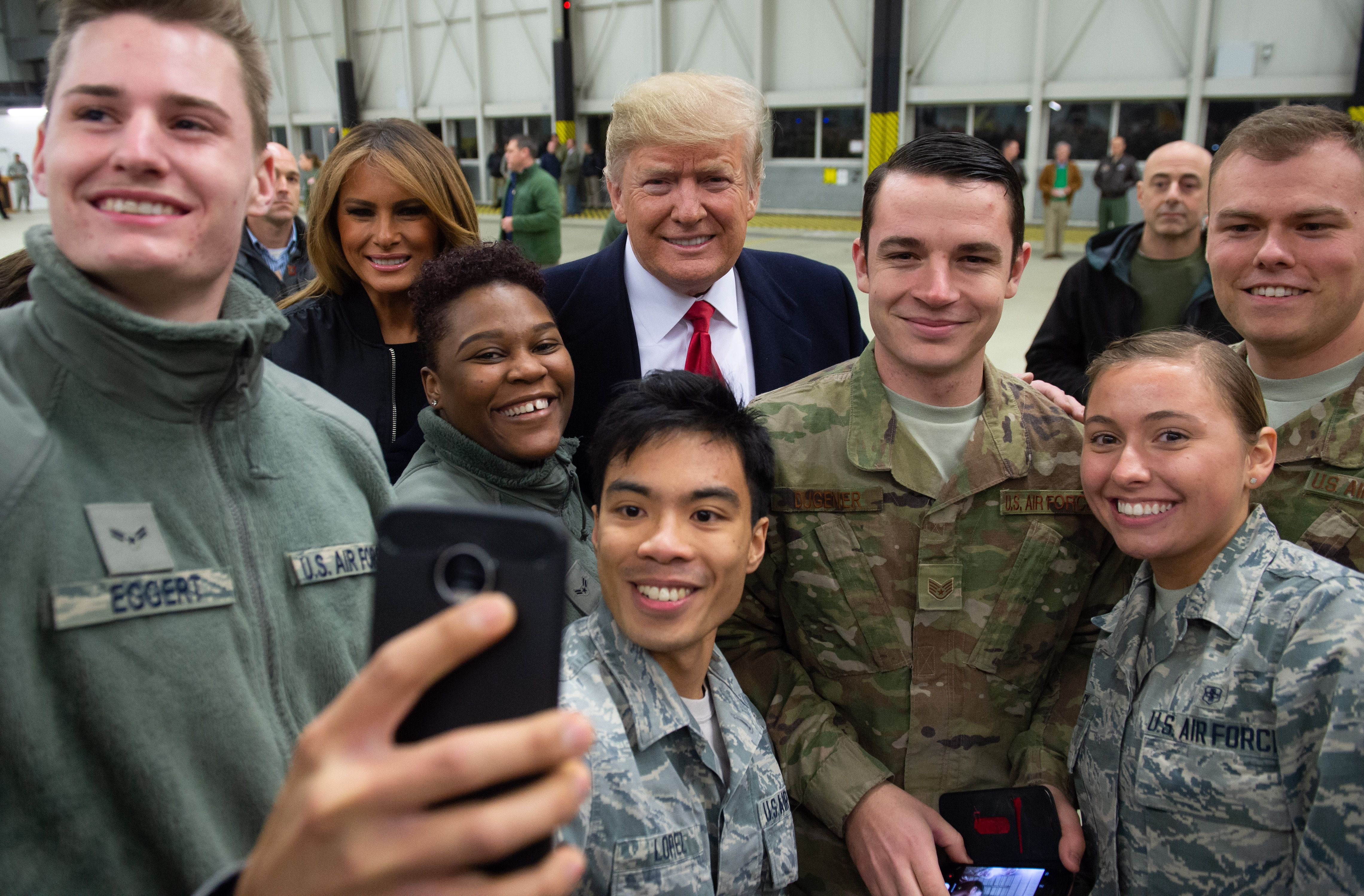 "US President Donald Trump and First Lady Melania Trump greet members of the US military during a stop at Ramstein Air Base in Germany, on December 27, 2018. - President Donald Trump used a lightning visit to Iraq -- his first with US troops in a conflict zone since being elected -- to defend the withdrawal from Syria and to declare an end to America's role as the global ""policeman."" (Photo by SAUL LOEB / AFP)"
