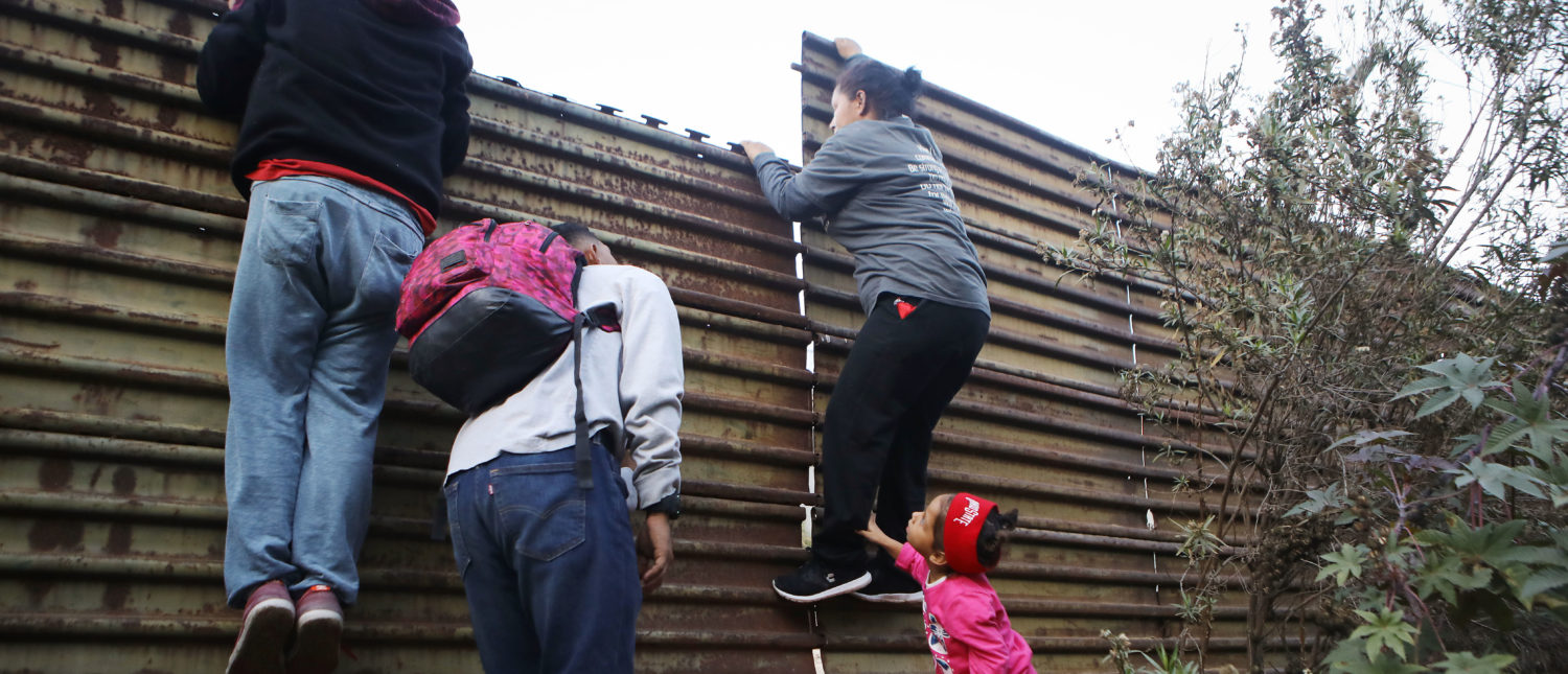 TIJUANA, MEXICO - DECEMBER 15: Honduran migrants, part of a caravan of thousands attempting to reach the U.S., peer across the U.S.-Mexico border fence on December 15, 2018 in Tijuana, Mexico. Many in the caravan had planned to request political asylum in the United States after traveling more than 6 weeks from Central America. U.S. border officials only process a limited numbers of asylum cases per day, leaving many migrants to choose between crossing illegally or possibly waiting for months in shelters in Mexico for U.S. asylum hearings. (Photo by Mario Tama/Getty Images)