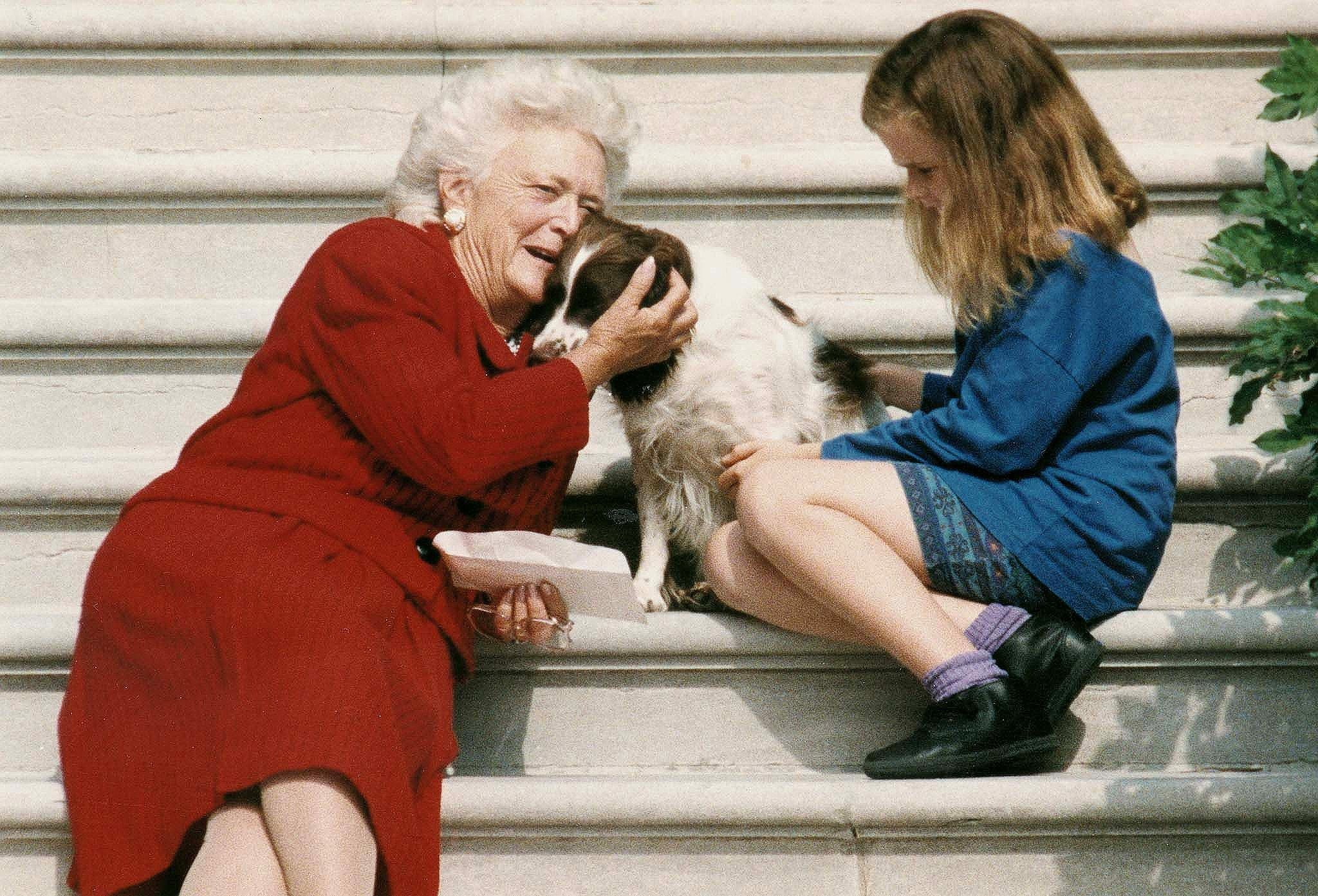 This file photo shows former First Lady Barbara Bush(L) talking to her dog Millie(C) as she and grandaughter Barbara Bush(R), age nine, wait for US President George Bush to return to the White House 13 September 1991, in Washington,DC. The President was undergoing a medical checkup at Bethesda Naval Medical Center. Grandaughter Barbara is the daughter of President George W. Bush. AFP PHOTO/Jennifer LAW
