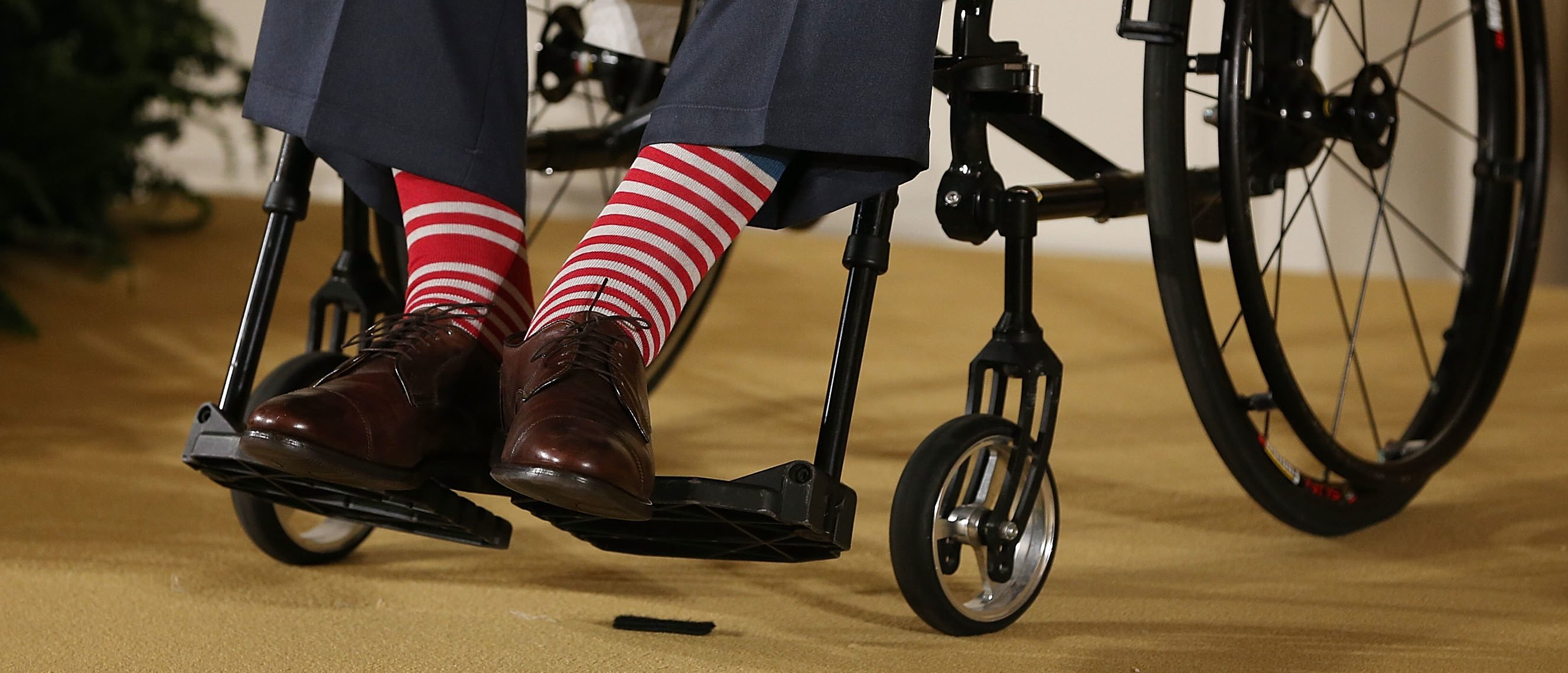 WASHINGTON, DC - JULY 15: Former President George H. W. Bush wears red stripped socks as he sits in a wheelchair during an event in the East Room at the White House, July 15, 2013 in Washington, DC. Bush joined President Obama in hosting the event to honor the 5,000th Daily Point of Light Award winner. (Photo by Mark Wilson/Getty Images)