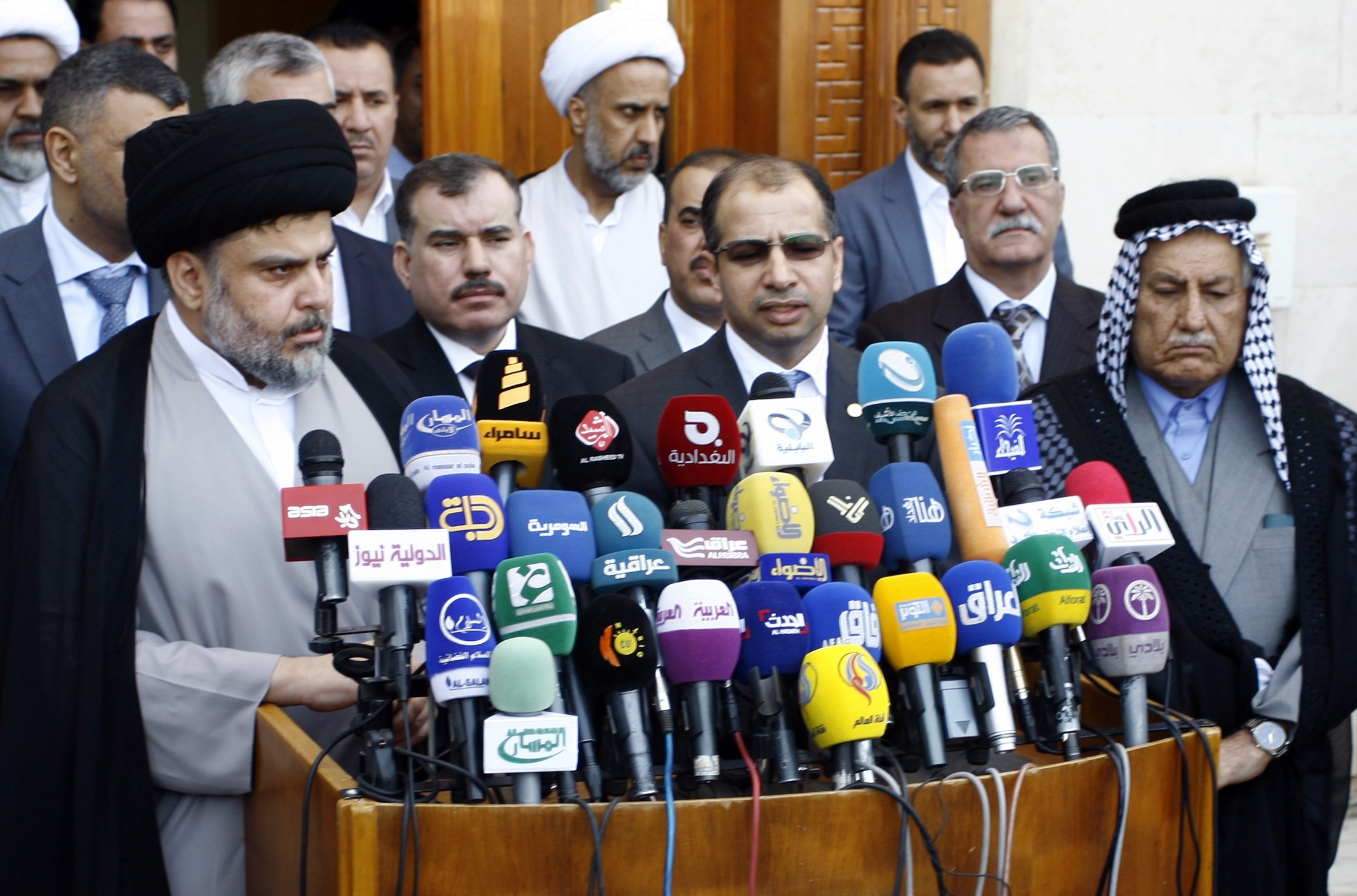 Iraqi Shiite cleric Moqtada al-Sadr (left) speaks to the press after a meeting with Salim al-Jabouri (second from right), the Parliament's speaker, alongside other parliament Sunni members on April 5, 2015 in the holy city of Najaf. (HAIDAR HAMDANI/AFP/Getty Images)