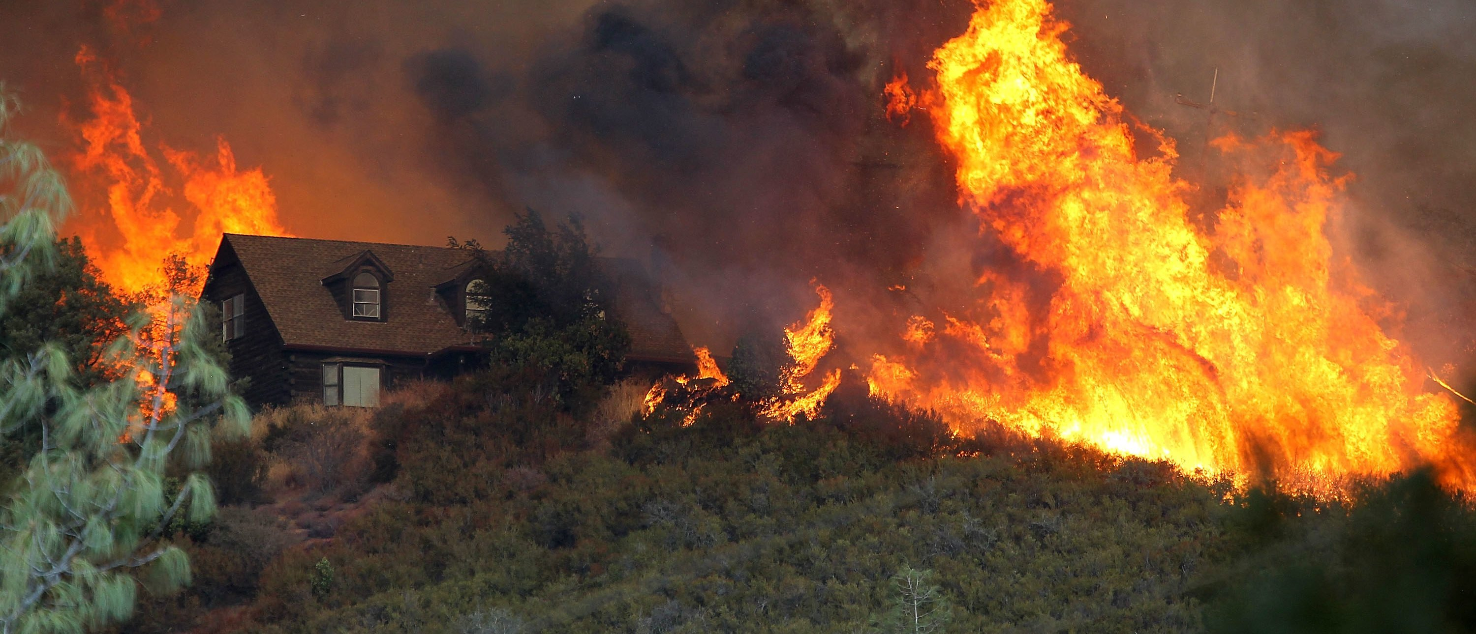 LOWER LAKE, CA - JULY 31: Flames from the Rocky Fire approach a house on July 31, 2015 in Lower Lake, California. Over 900 firefighters are battling the Rocky Fire that erupted to over 15,000 acres since it started on Wednesday afternoon. The fire is currently five percent contained and has destroyed three homes. (Photo by Justin Sullivan/Getty Images)
