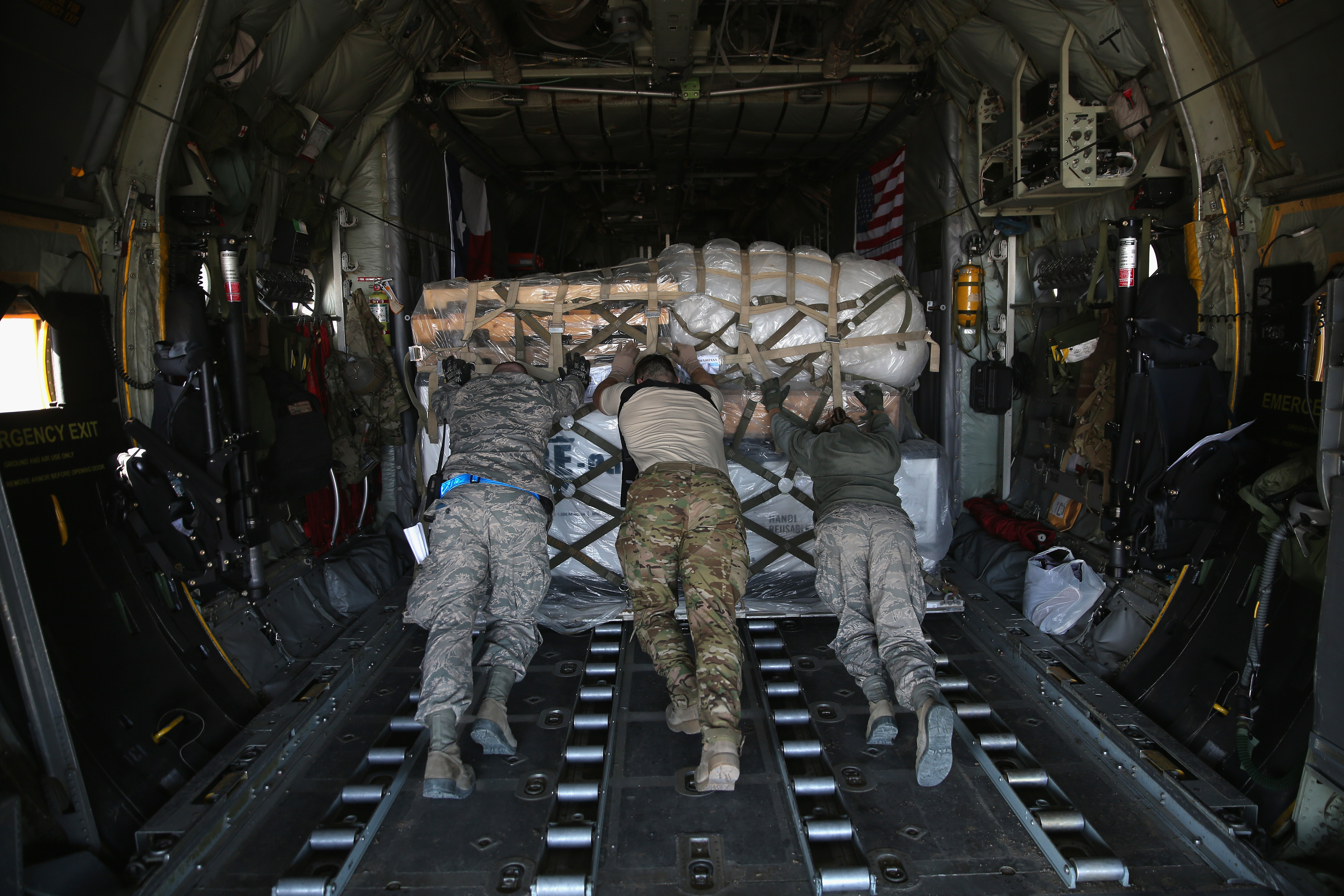 U.S. Air Force service members push cargo onto a Texas Air National Guard C-130 cargo plane bound for Iraq on January 10, 2016 from a base in an undisclosed location in the Persian Gulf Region. (Photo by John Moore/Getty Images)
