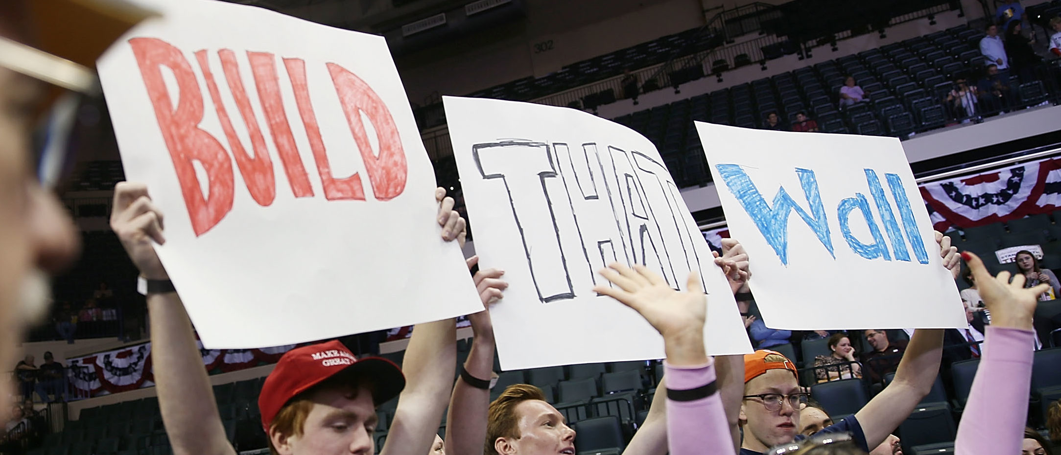"""TAMPA, FL - FEBRUARY 12: People hold signs that read, """" Build that Wall"""", as they wait for the start of a campaign rally for Republican presidential candidate Donald Trump at the University of South Florida Sun Dome on February 12, 2016 in Tampa, Florida. The process to select the next Democratic and Republican Presidential candidate continues. (Photo by Joe Raedle/Getty Images)"""