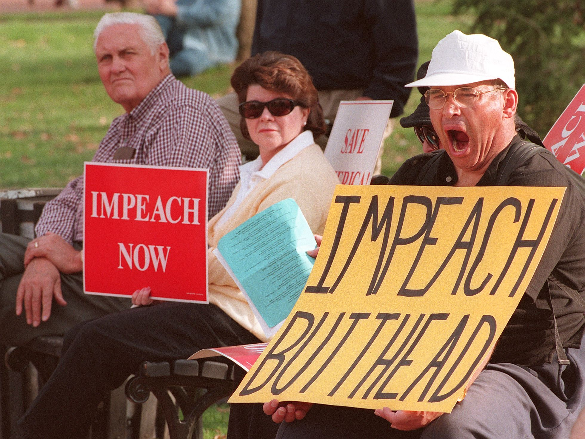 Unidentified protestors demanding the impeachment of US President Bill Clinton conduct their noontime protest from the park benches in Lafayette Park across from the White House 07 December. (Photo credit should read PAUL J. RICHARDS/AFP/Getty Images)