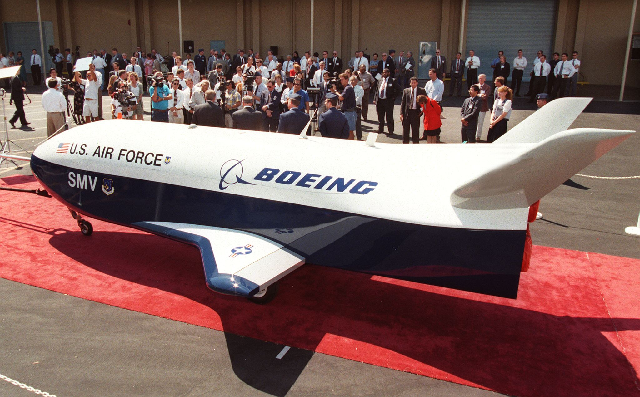 SEAL BEACH, UNITED STATES: A prototype of a Space Maneuver Vehicle (SMV), built by the US Air Force and Boeing, is rolled out during a ceremony at Boeing's facility in Seal Beach, CA, 03 September. The 22-foot long vehicle with a 12-foot wing span is a 90-percent scale version which will be flight tested and eventually used as part of the Air Force's Military Spaceplane program. The program will include this small, unpiloted, powered spacecraft to be used as reusable satellite for missions such as tactical reconnaissance and space object identification and surveillance. AFP PHOTO Vince BUCCI