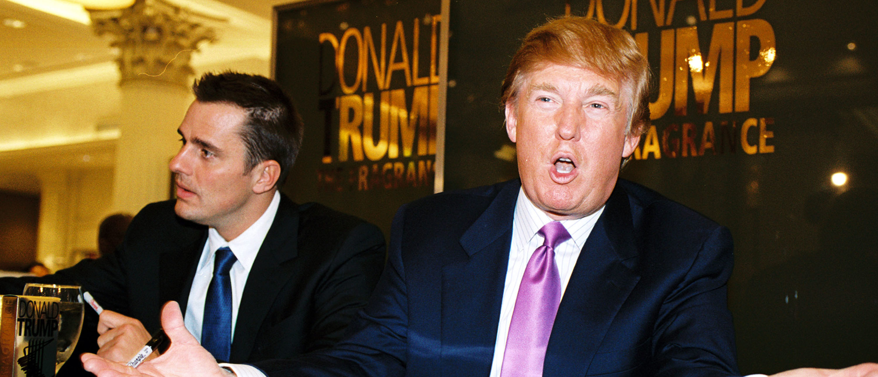 """CHICAGO - DECEMBER 7: Real estate mogul Donald Trump (R) and """"The Apprentice"""" winner Bill Rancic (L) make a promotional appearance at Marshall Field's for Trump's new cologne, The Fragrance, December 7, 2004 in Chicago, Illinois. (Photo by Scott Harrison/Getty Images)"""